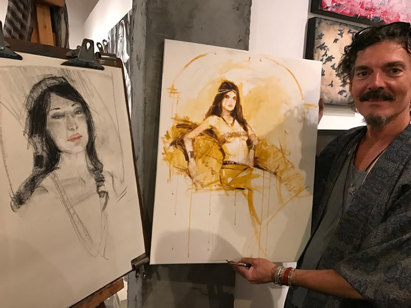 Bill Mather showcasing two of his paintings from the night.