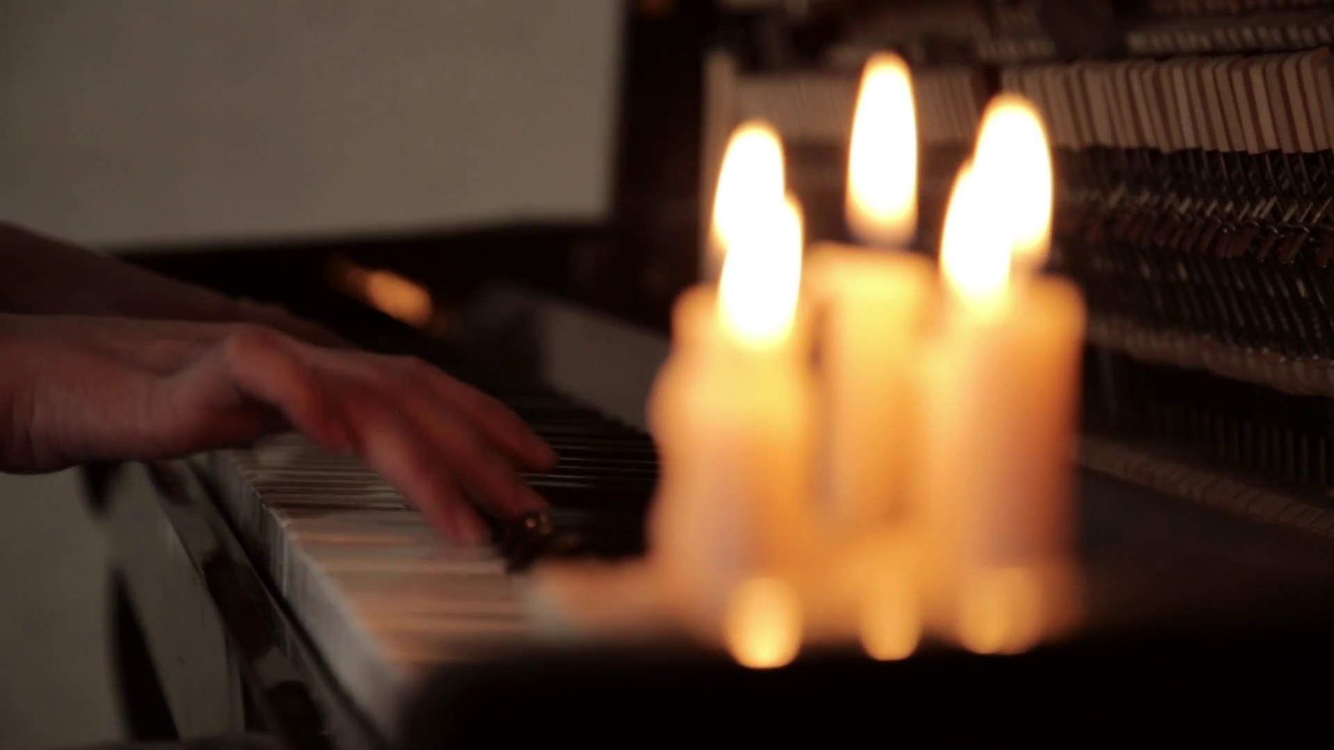 videoblocks-close-up-female-hands-playing-piano-on-a-dark-in-a-candles-light_hy6dg1ptx_thumbnail-full01.png