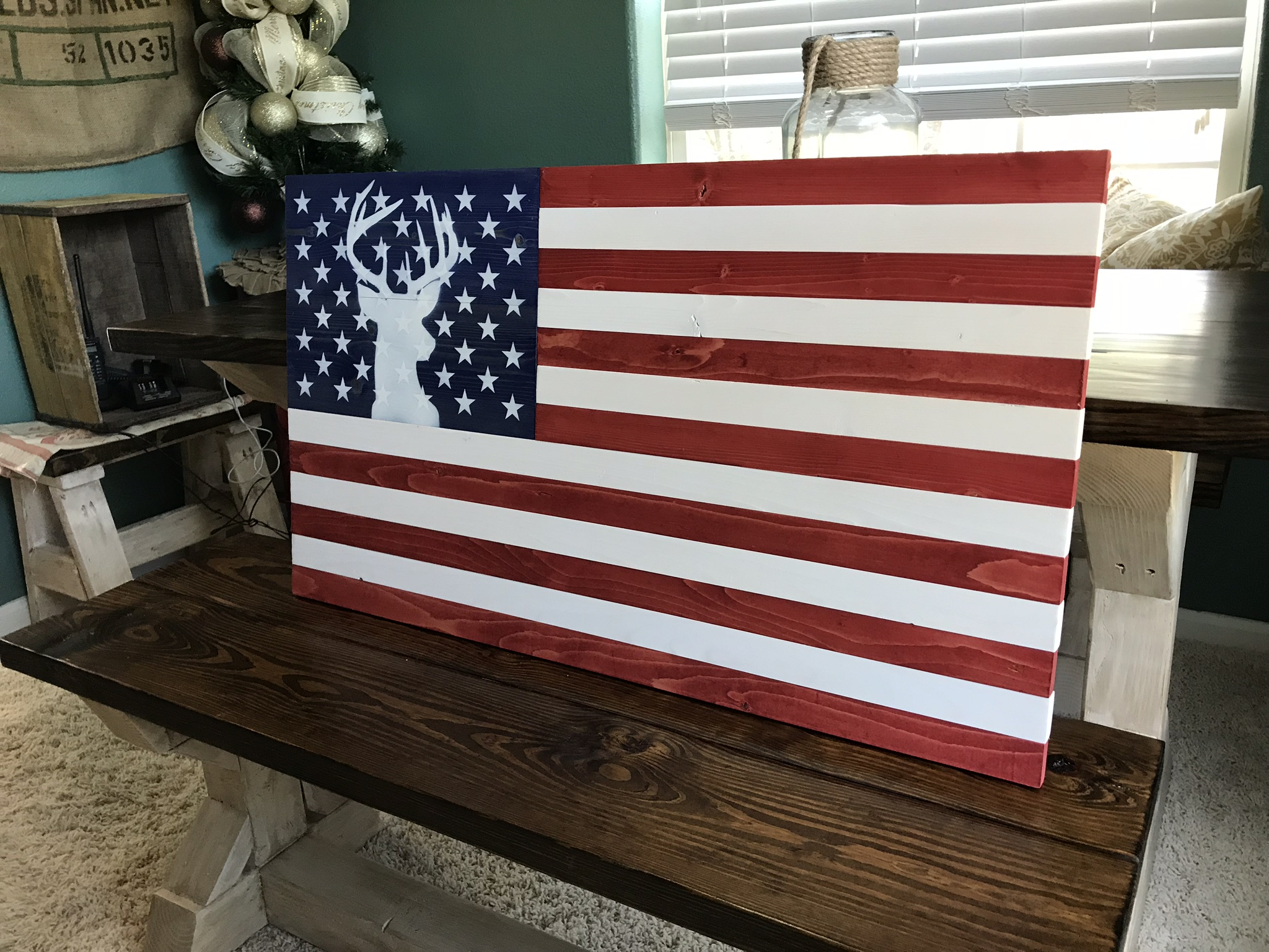 This American Flag features the silhouette of a buck deer in the Union. Stained red, white, and blue with the painted stag in the union. Show your love for the white tail buck and America!