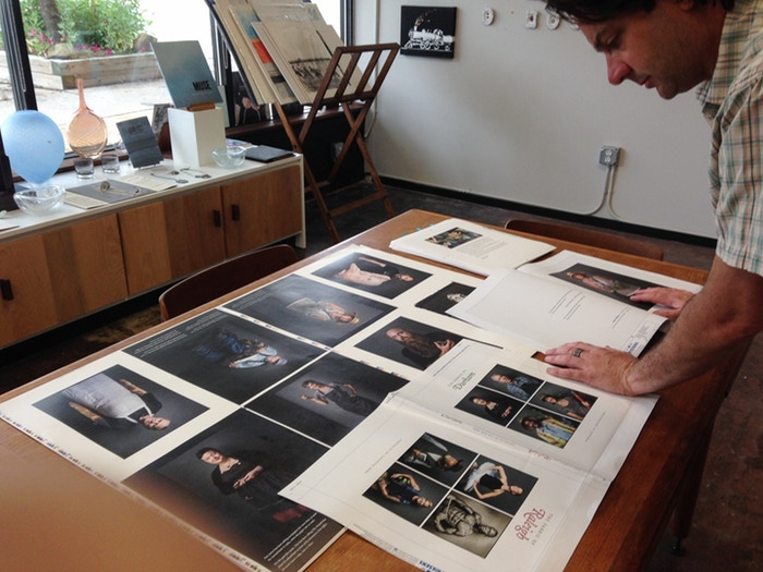 Checking press proofs to ensure images are reproducing as expected before signing off on production.