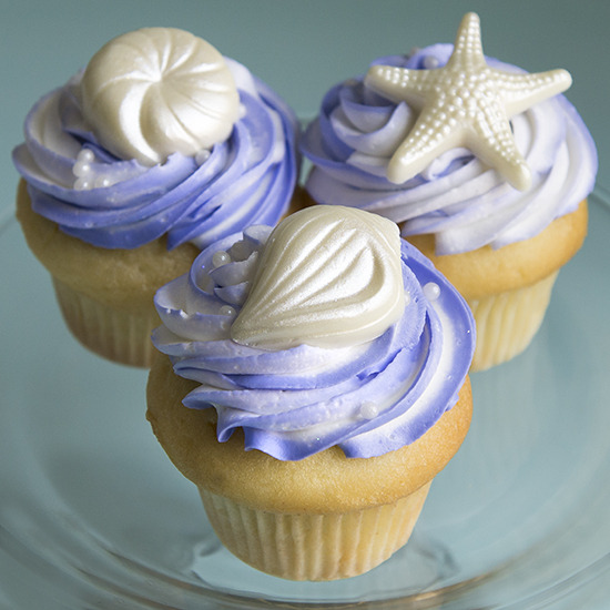 Beach Themed - Your choice of colors added to the frosting adding white chocolate seashells/starfish. $4.25 each, minimum of one dozen per flavor and design.