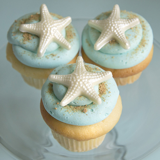 Beach Themed - Vanilla, chocolate, lemon, almond or strawberry cupcake, vanilla buttercream frosting. White chocolate starfish with graham cracker sand. Color of your choice: $4.25 each, minimum of one dozen per flavor and design.