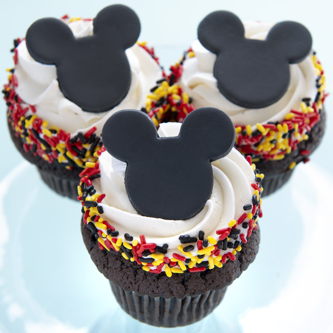 Mickey - Vanilla, chocolate, lemon, almond or strawberry cupcake, vanilla buttercream frosting, red and yellow sprinkles, black fondant mickey silhouette. $4.00 each, minimum of one dozen.