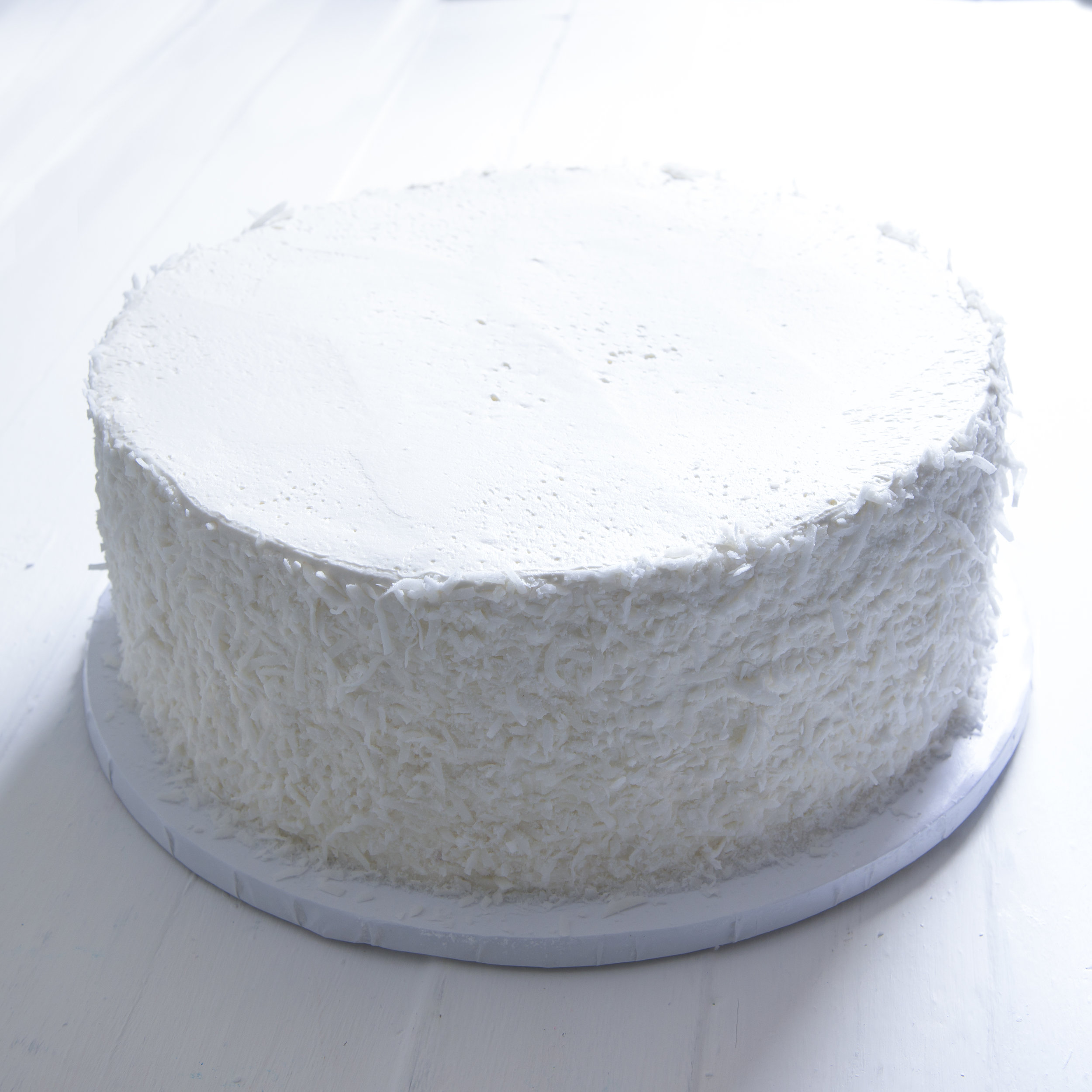Snowball - Vanilla cake, filled with coconut buttercream, frosted with vanilla buttercream, sides covered in fresh coconut.6