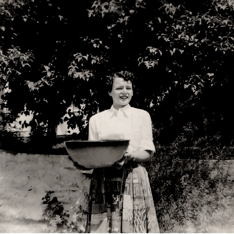 An unexpected reunion. - Pictured here is the happy customer who, in 1949, commissioned Peter Pots of Providence (as we were called at the time) to make her a Punch Bowl. This was the one and only bowl of this stature ever made by us, requiring the kiln to be rebuilt at the time to even fire it. The creation of this bowl was such an endeavor, we couldn't let it leave without first snapping a photograph.This photo was all that remained with us of this Punch Bowl, until 2013, when a most unexpected reunion occurred.Attending the General Stanton's Flea Market in Charlestown, RI, this bowl's maker, Oliver Greene, once again found himself in its presence. After some questions as to where it was found, and a little explaining he, in fact, was the creator of this enormous bowl, Oliver convinced the vendor to trade it to him for eight Dinner Plates.This very bowl can now be seen on display here in our showroom. As many customers have inquired about this bowl, and about us making a larger bowl, in general, we thought why not pay homage to this stunning piece. Our new Benefit Street Bowl is very similar, though not identical, making the original still the one and only ever made.