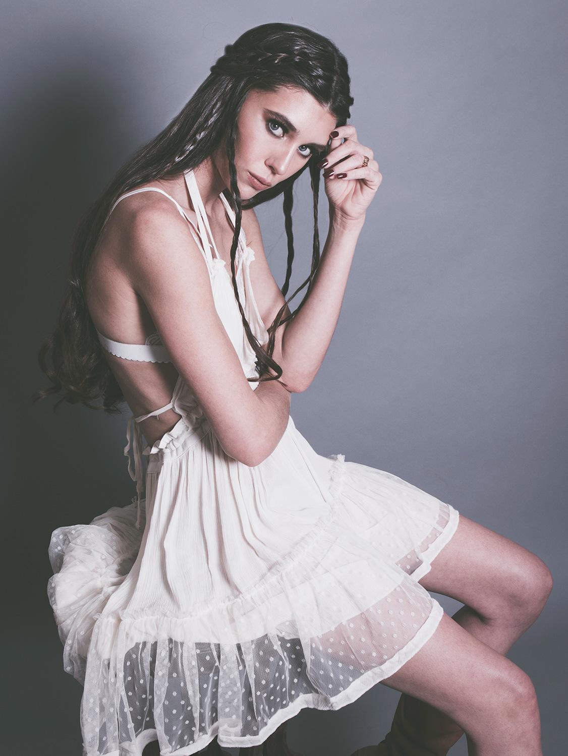 amora_beauty_studio_female_model_sitting_chair_white_dress_indie_rock__braids_miami.jpg