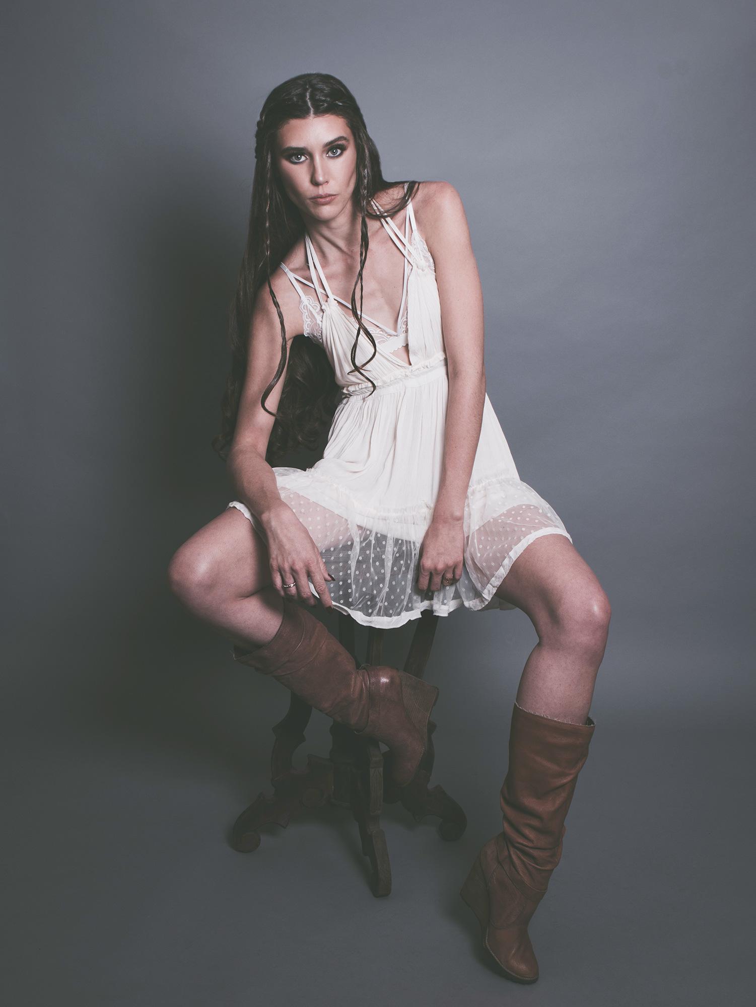 amora_beauty_studio_female_model_sitting_chair_white_dress_indie_rock_braids_country_miami.jpg