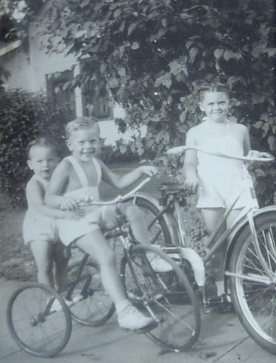 """This pic was taken in Minneapolis, MN in the early-mid 1940s. My sister, Louise Cohen, is standing adjacent to her 24x2.125 wheel bike, I am sitting on the large tricycle, and my younger brother, Leo Cohen Jr. is standing on the rear axle of the tricycle. Both of my siblings were involved in the bicycle business and unfortunately both have passed away.""  Howie, Leo Jr & Puss on trike & bike [c.1942-43] @1985"