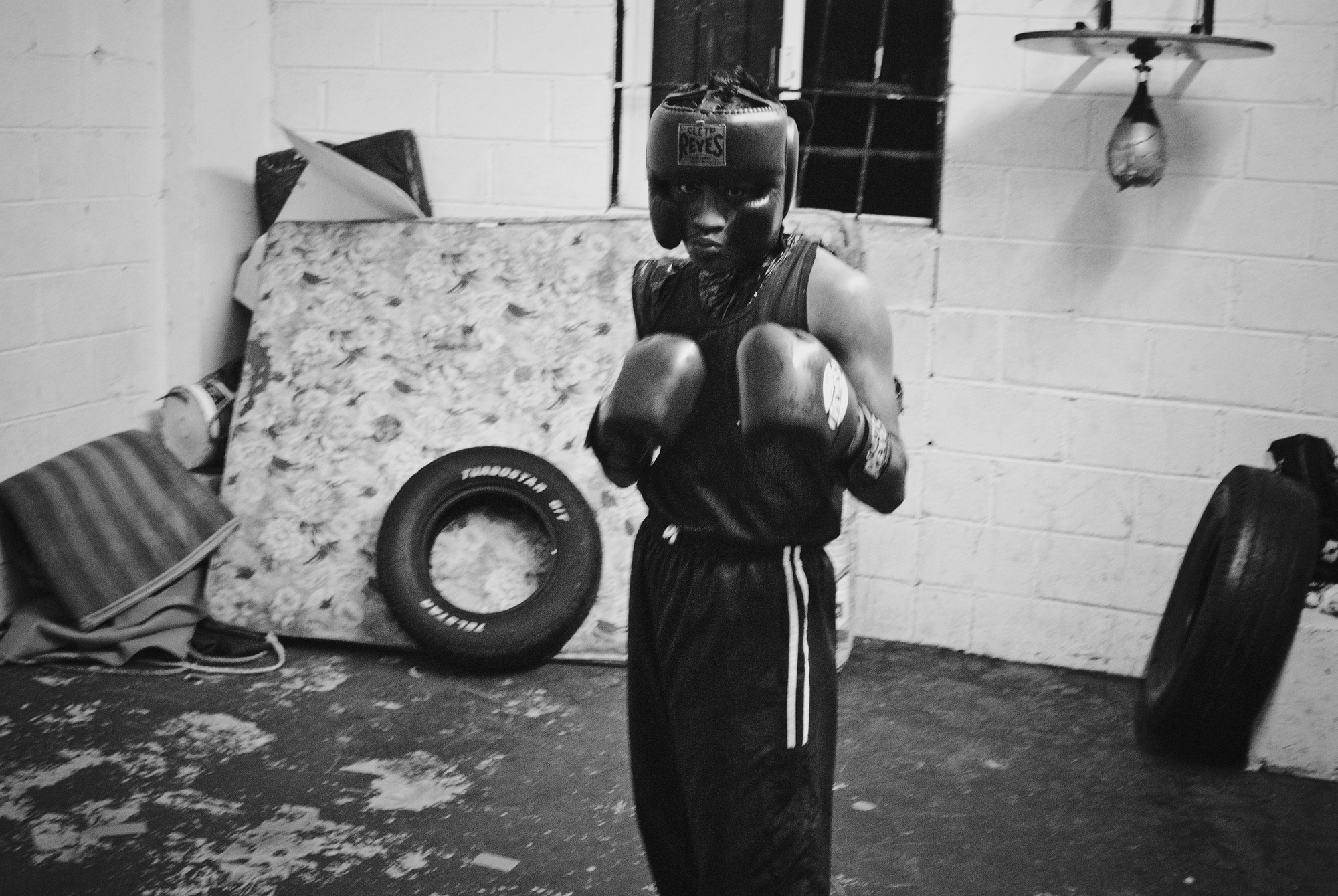 Young amateur boxer gives the stance in coach Cervantes's boxing gym.