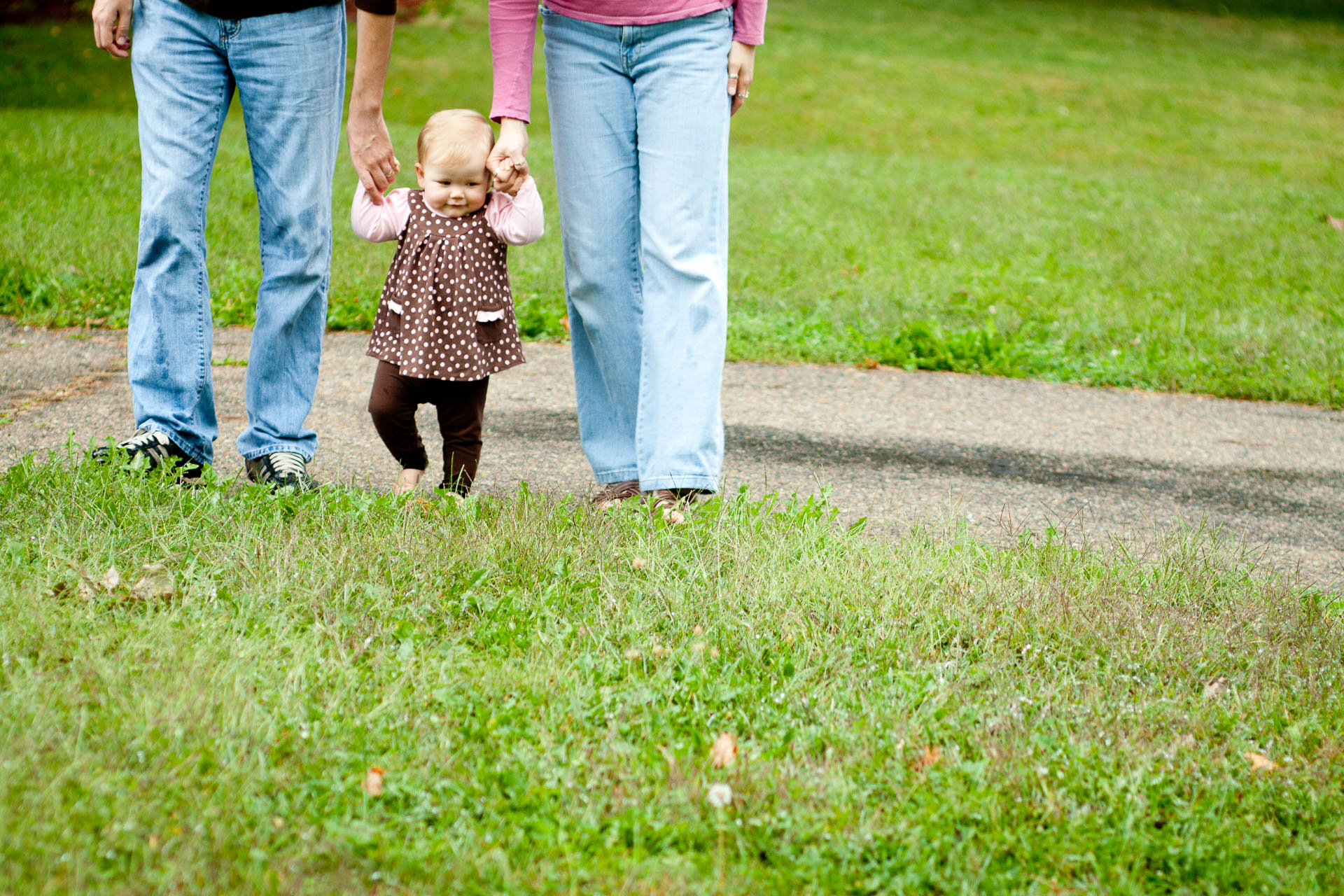 Toddler walking with mom and dad