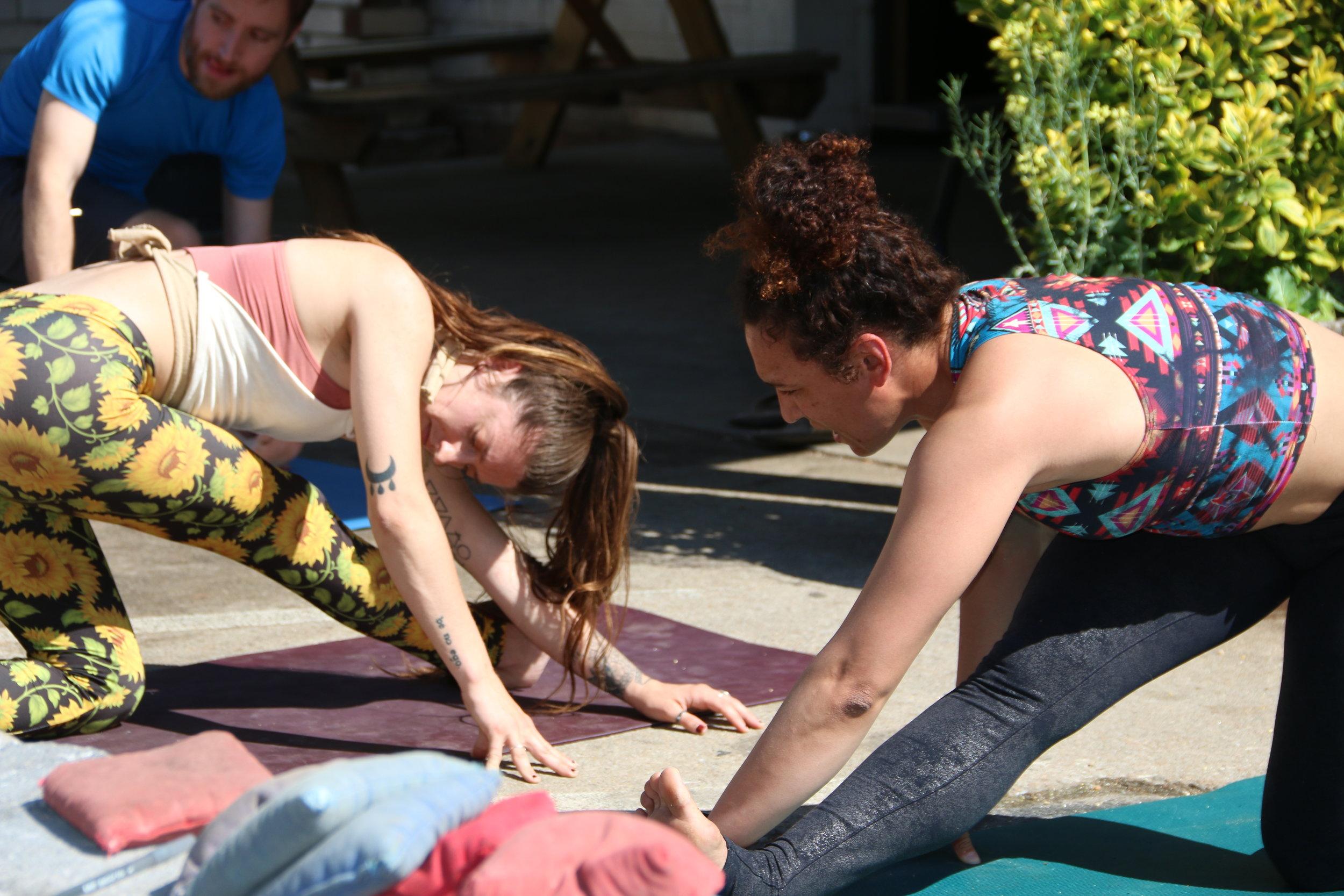 Cici and Erica co-teaching an outdoor yoga class