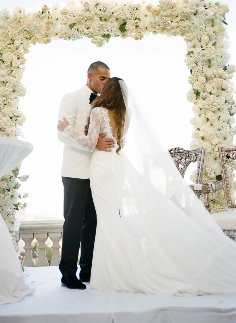 Oversized White Frame Ceremony with white hydrangea, orchids, roses, stock, and spray roses in various stages of growth.