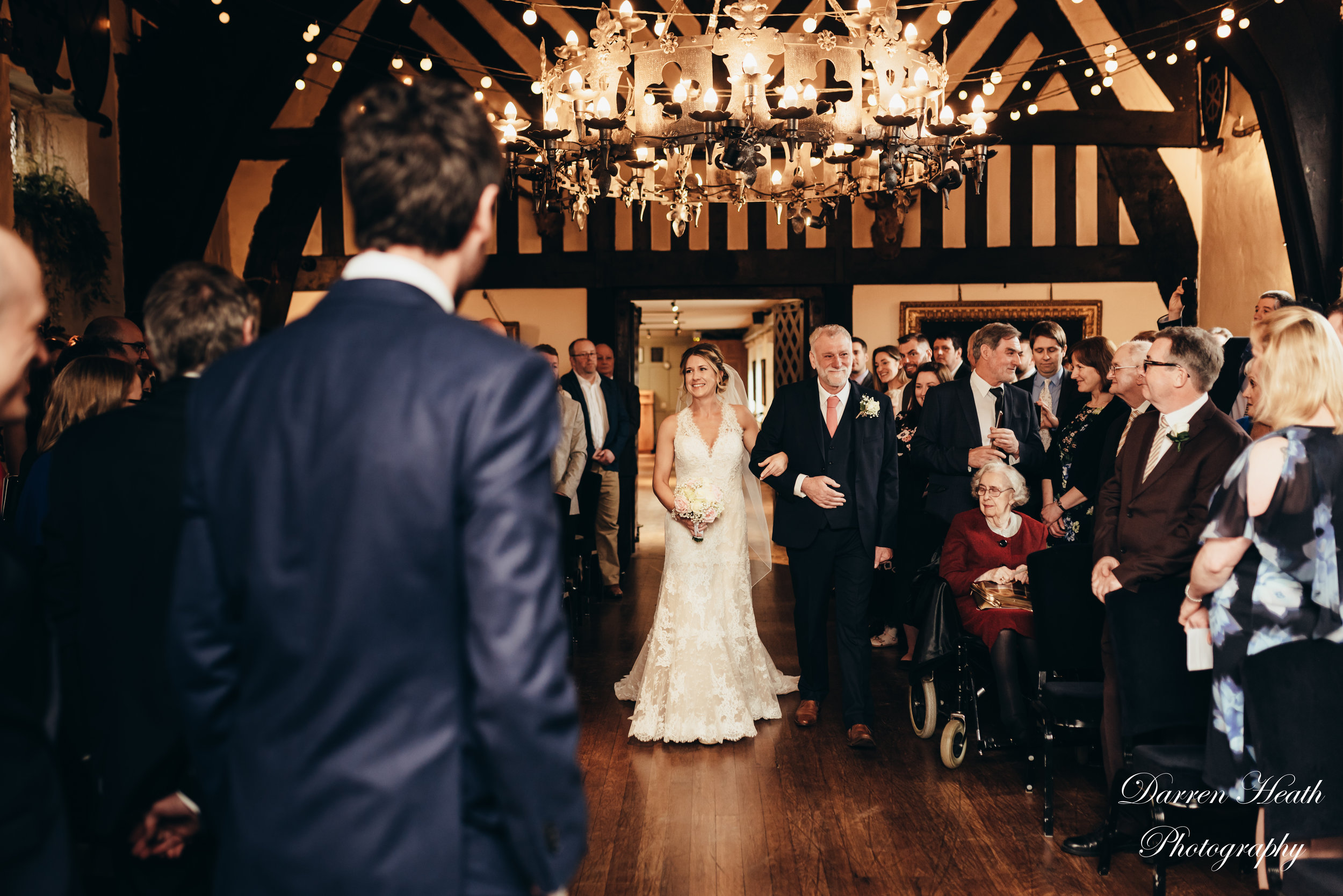 Bride walked down the aisle by proud father, as the groom watches