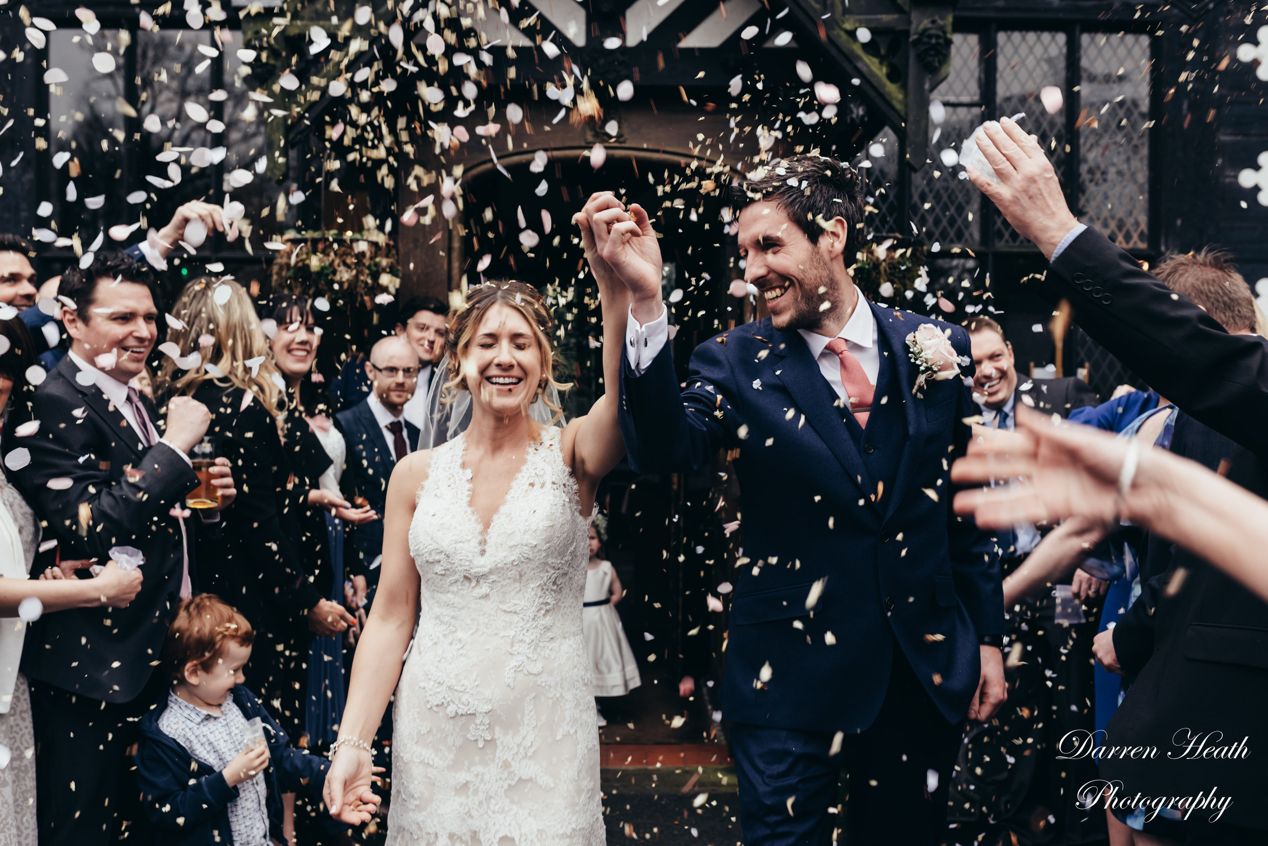 Bride and Groom walk out of Samlesbury Hall to a confetti storm