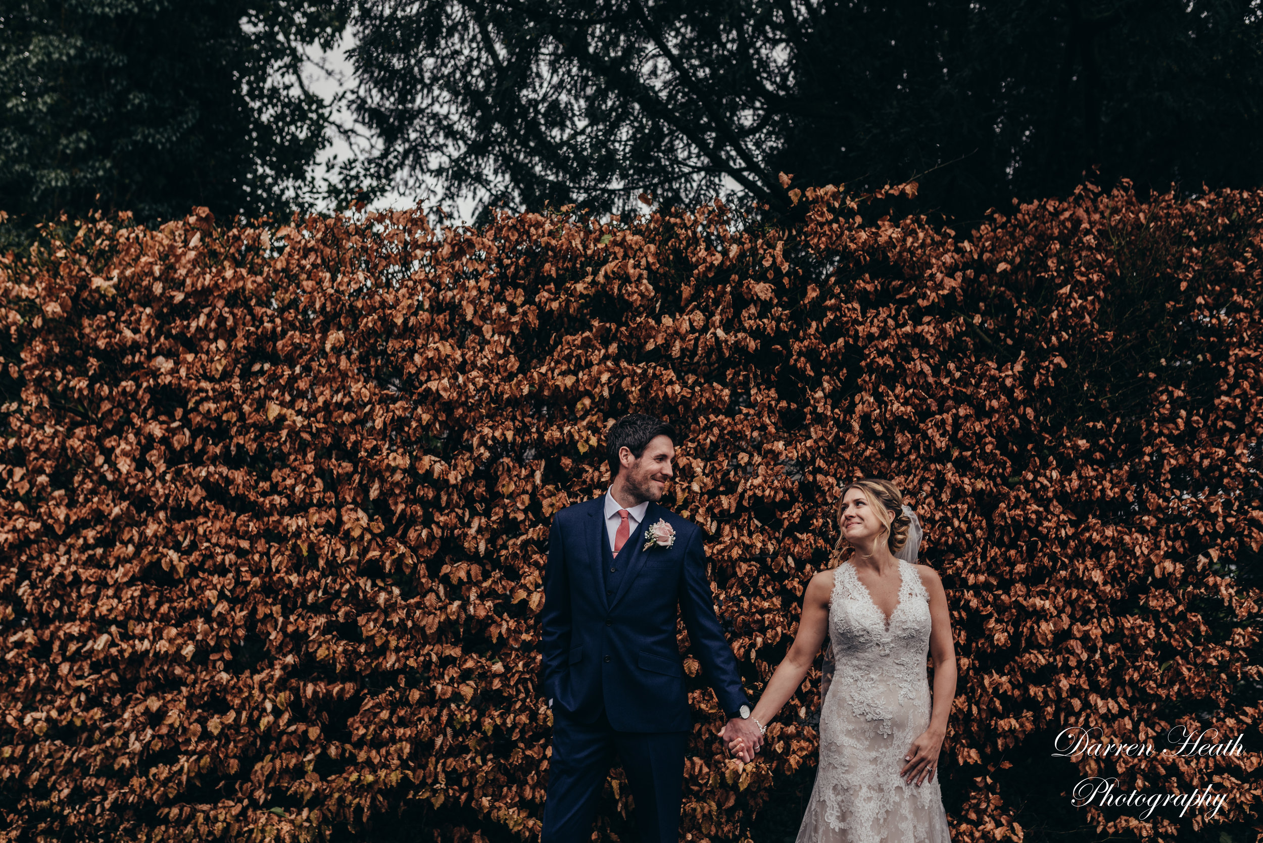 Autumnal Coloured leaves give back drop to bride and groom