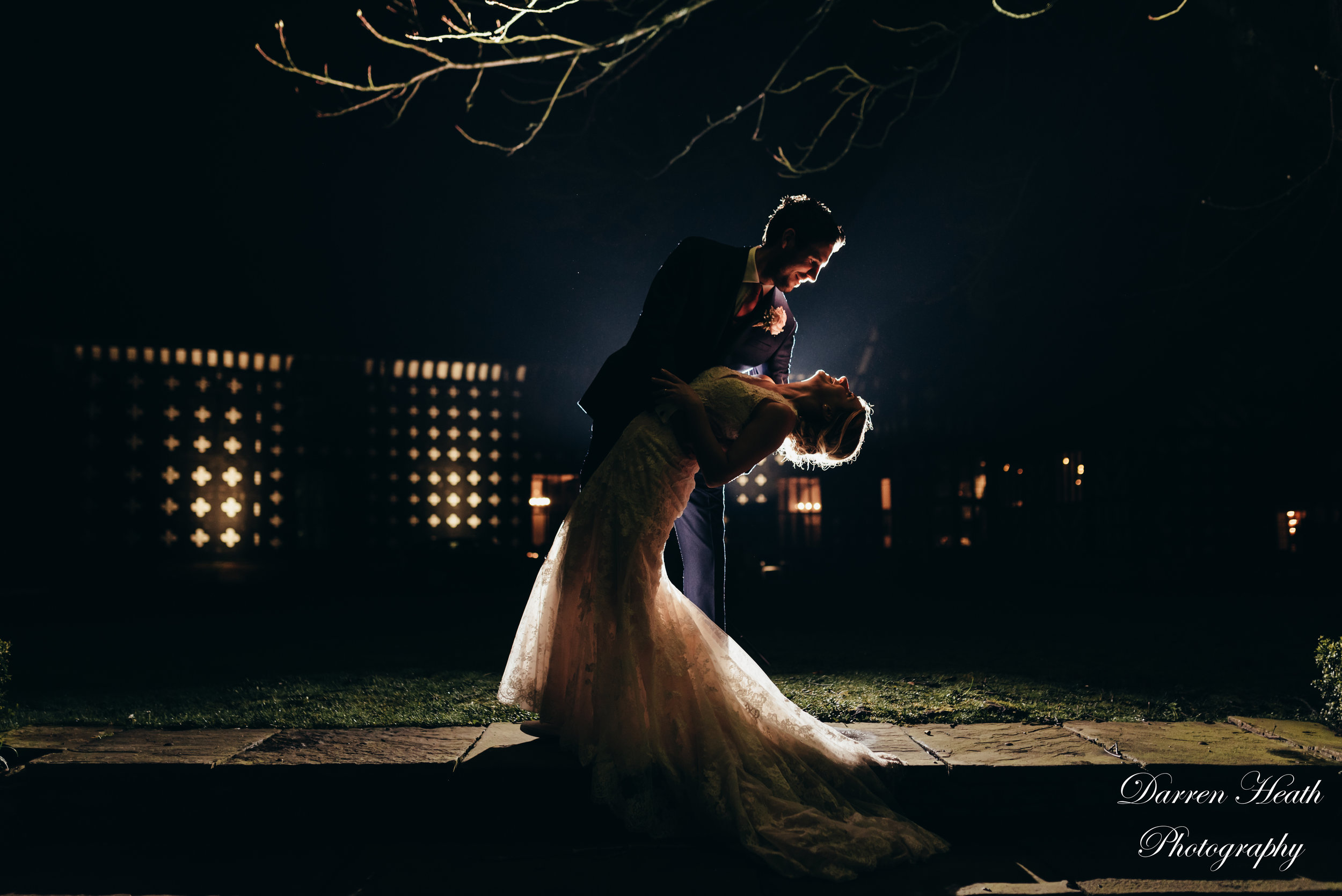 Nighttime backlit bride and groom portrait outside Samlesbury Hall