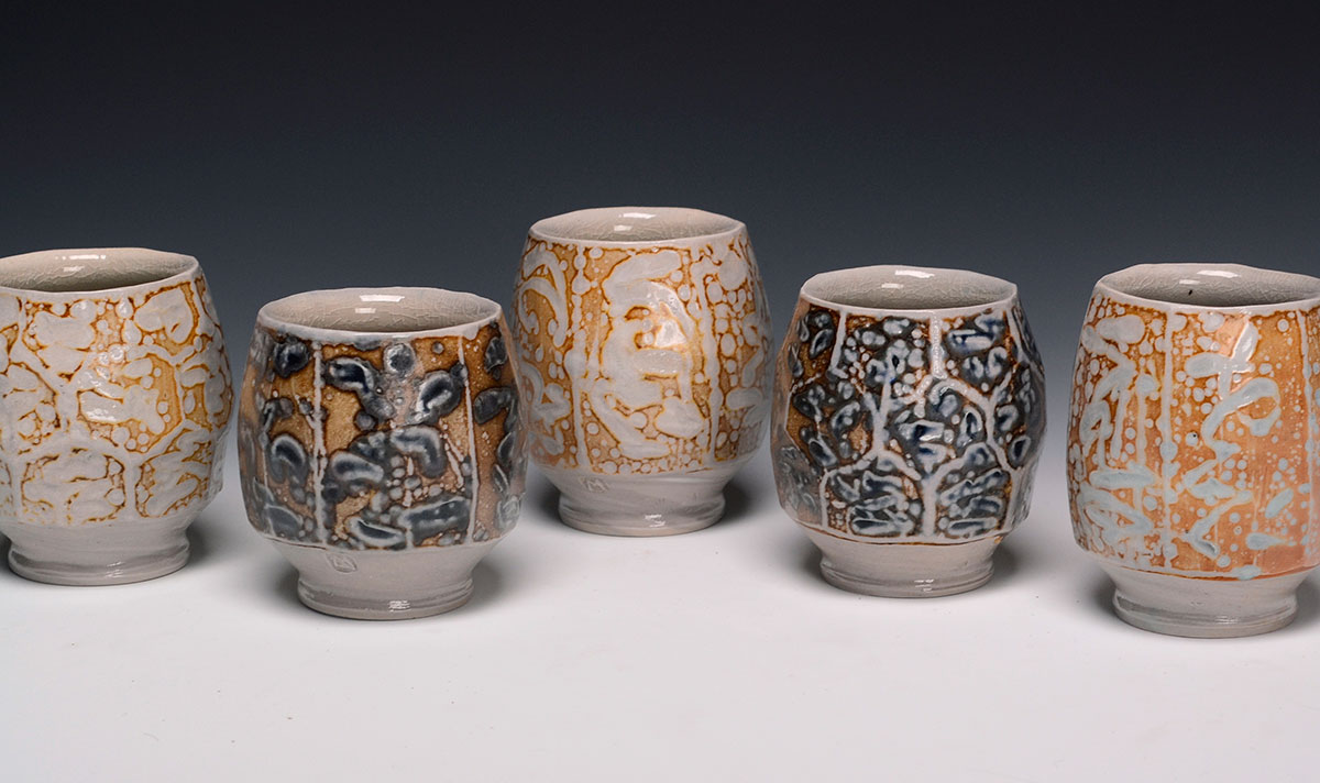 Five faceted cups with markings