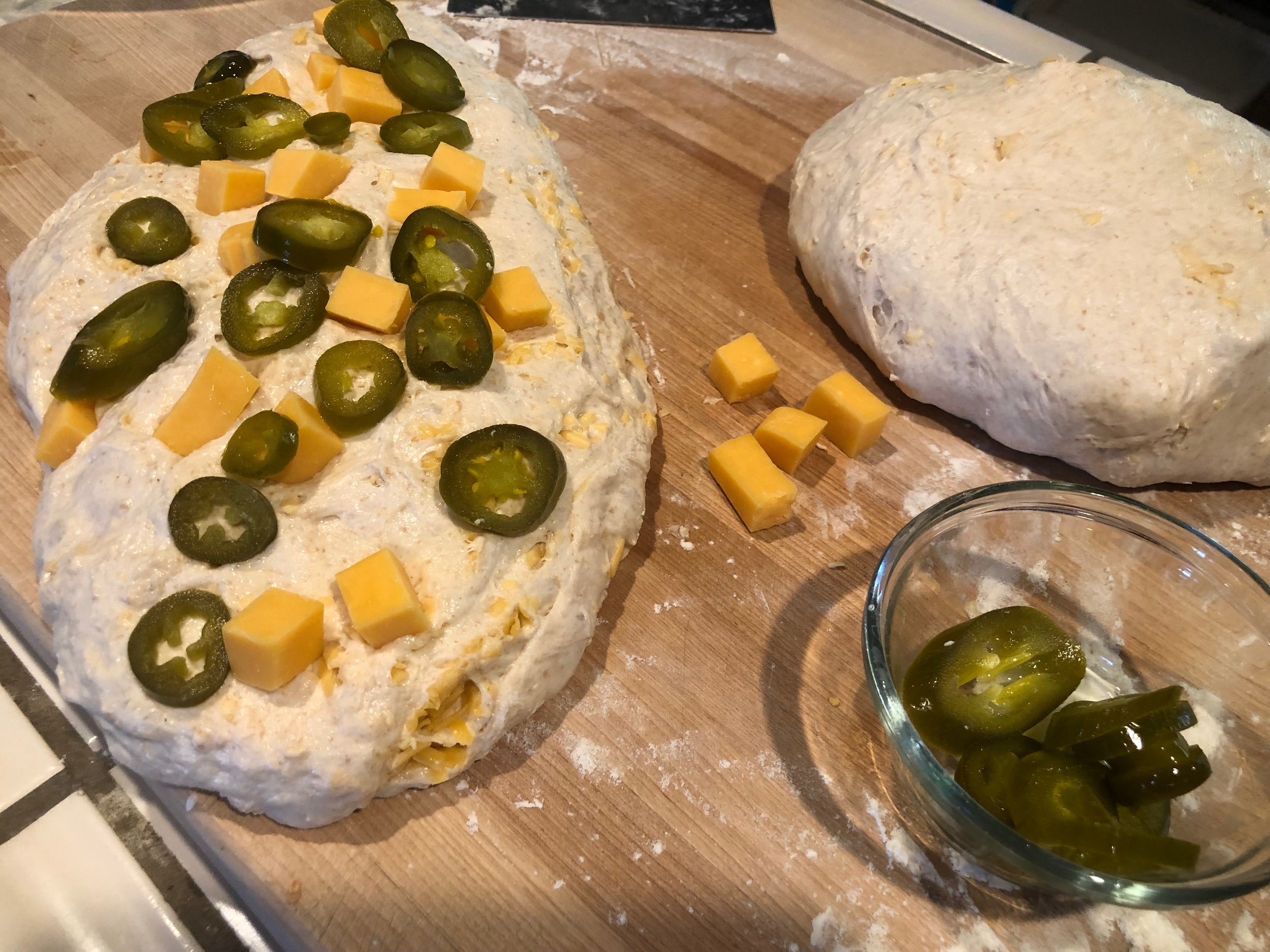 Again layer the cheddar cubes and jalapenos into the dough will shaping for bench rest.
