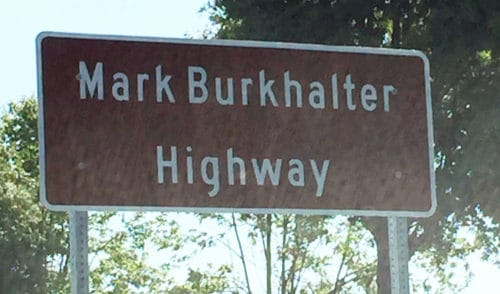 Georgia's Department of Transportation (GDOT) is responsible for the maintenance of 141. Travelers may note the signs declaring that roadway through Johns Creek has been dedicated as Mark Burkhalter Highway.