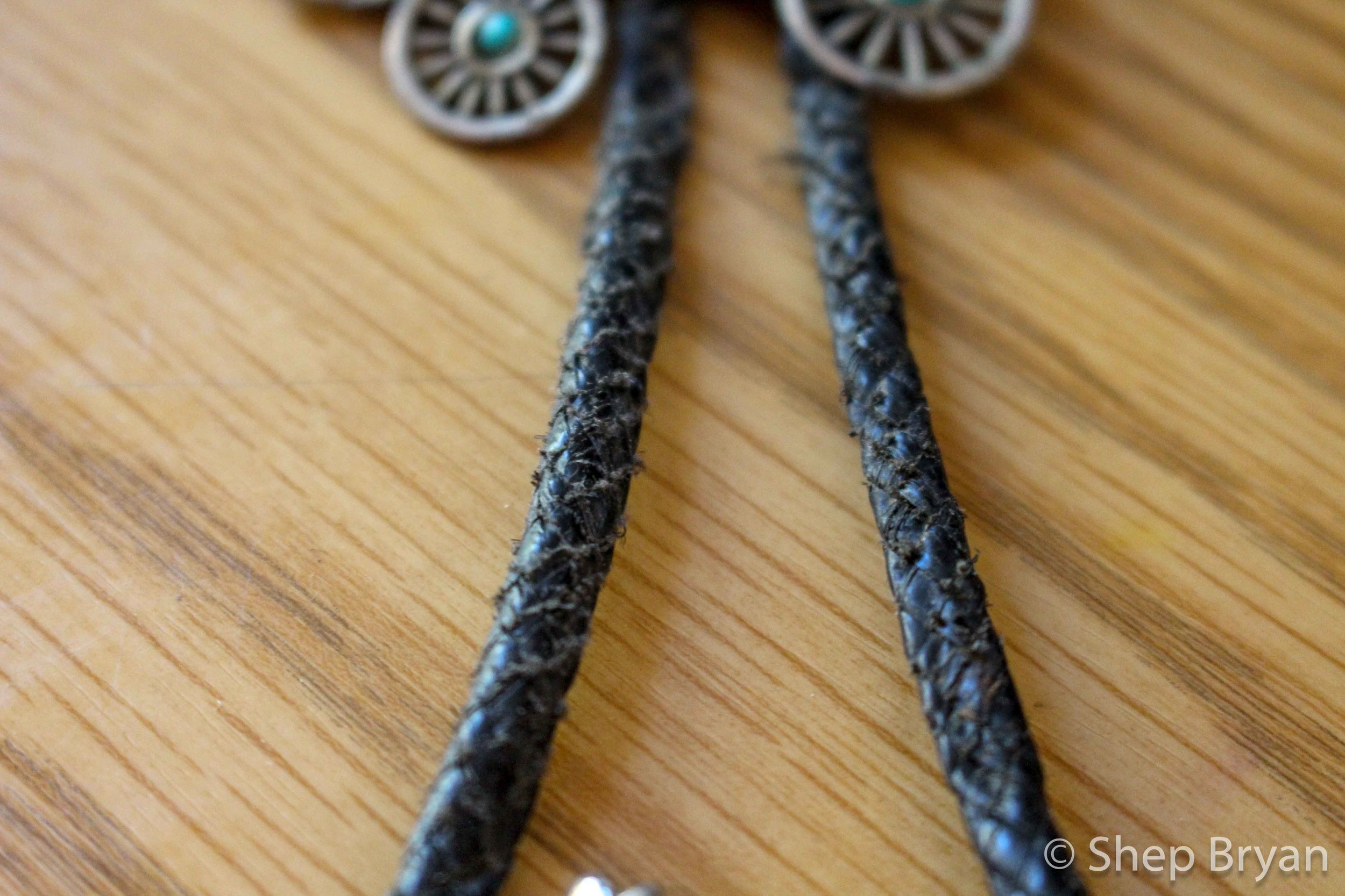 Up close & personal with a vinyl bolo cord that has seen better days.