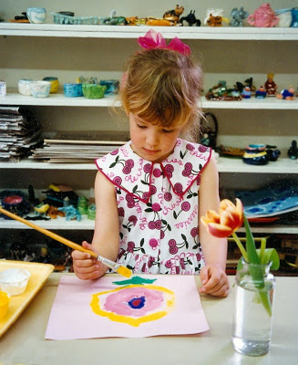 This student is painting a flower in the style of Georgia O'Keeffe.