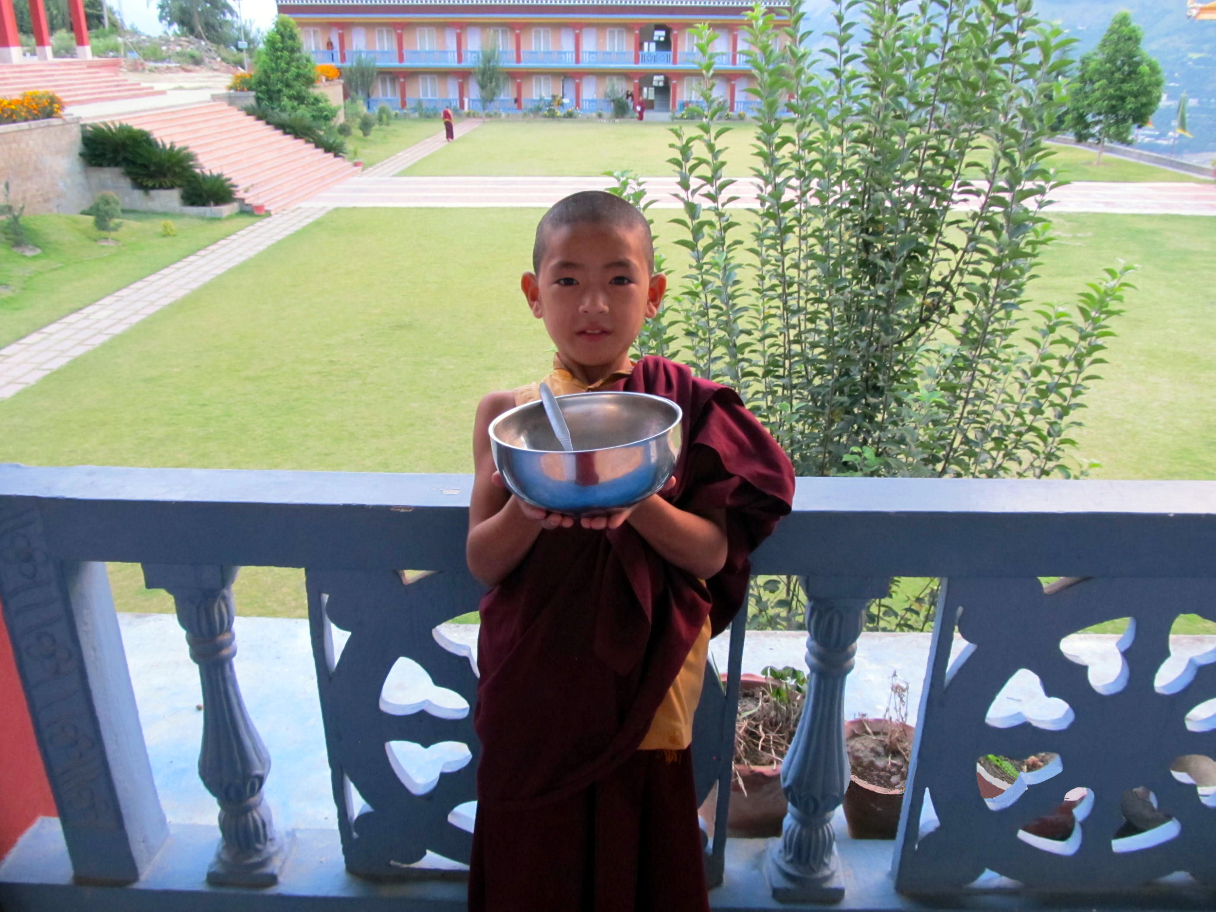 A young monk posted at the corridor of Dechen Choekhor monk's hostels before heading for dinner with his alms bowl.