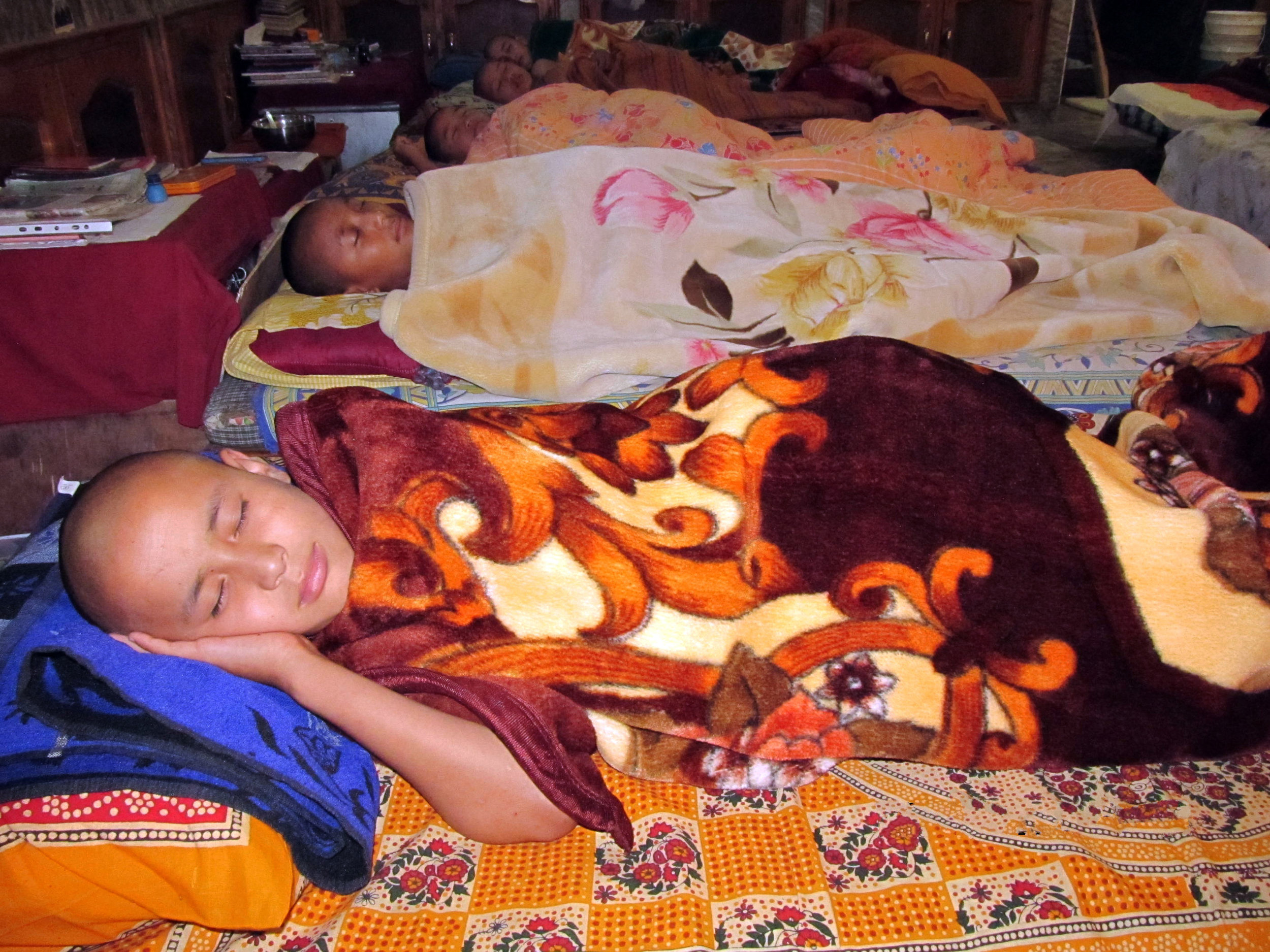 Young monks sleeping in the temporary quarters during winter while waiting for the completion of their hostels.