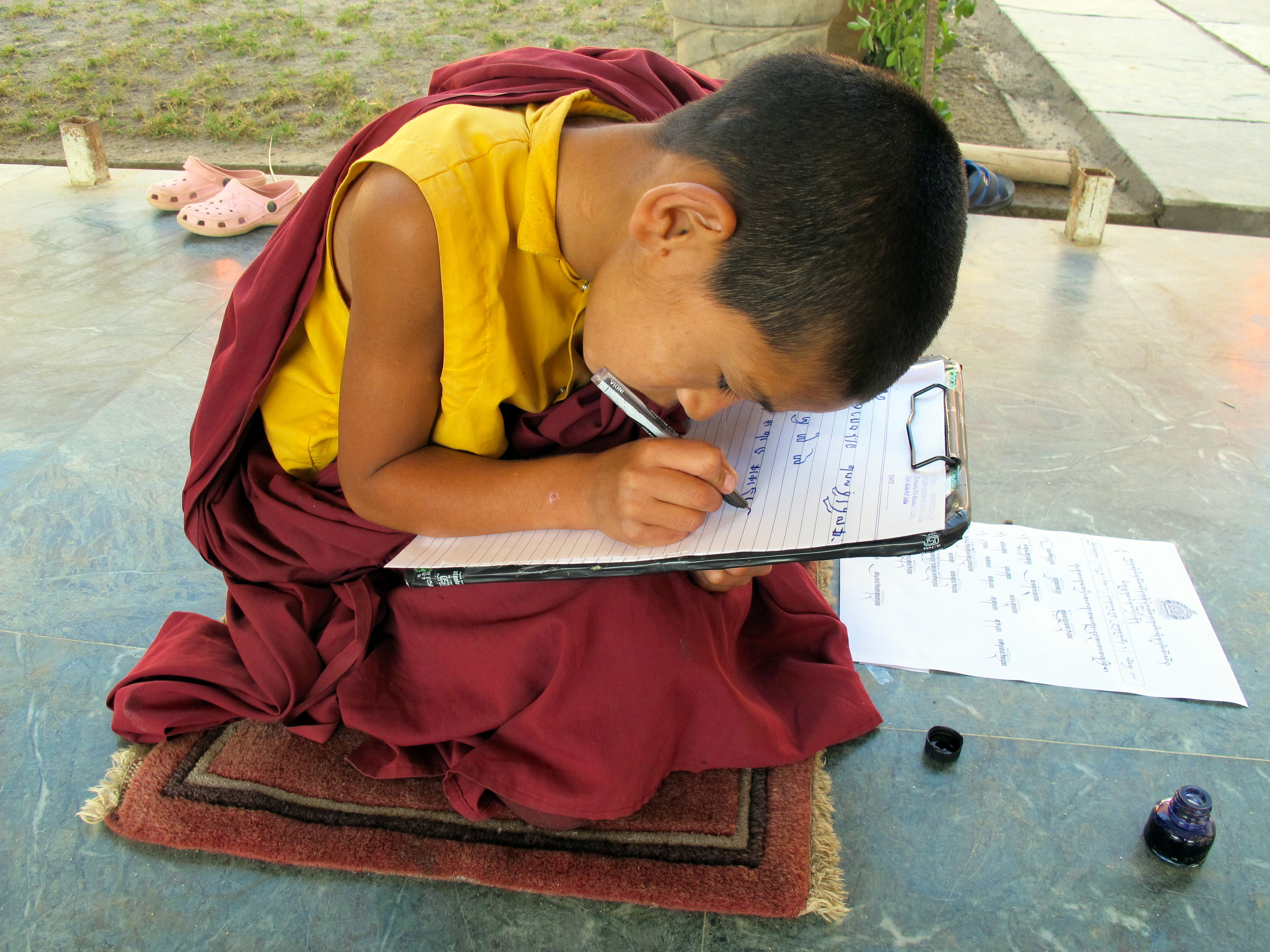 A young monk taking the yearly evaluation examination of Dechen Choekhor Mahavihara.