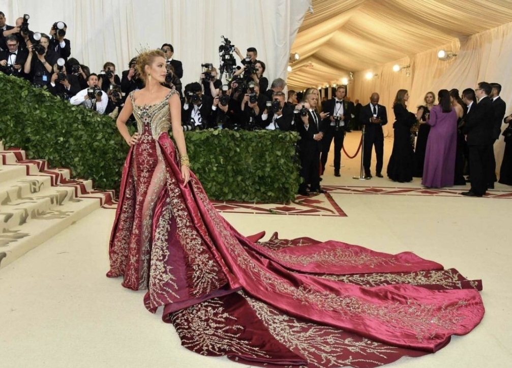 """- American based actress Blake Lively attended this years 2018 Met Gala. The themed was """"Heavenly Bodies: Fashion and the Catholic Imagination.� Lively made the decision for Donatella Versace to dress her for this years theme. This isn't a surprise at all. Following her career as an actress her style speaks volume in its own race. The pair decided to go with not something drastic but simple, chic, and fun, wearing an rich crimson custom Versace gown. Versace as we know is based in Italy and currently makes gowns, suits and preference costumes for celebrities etc."""