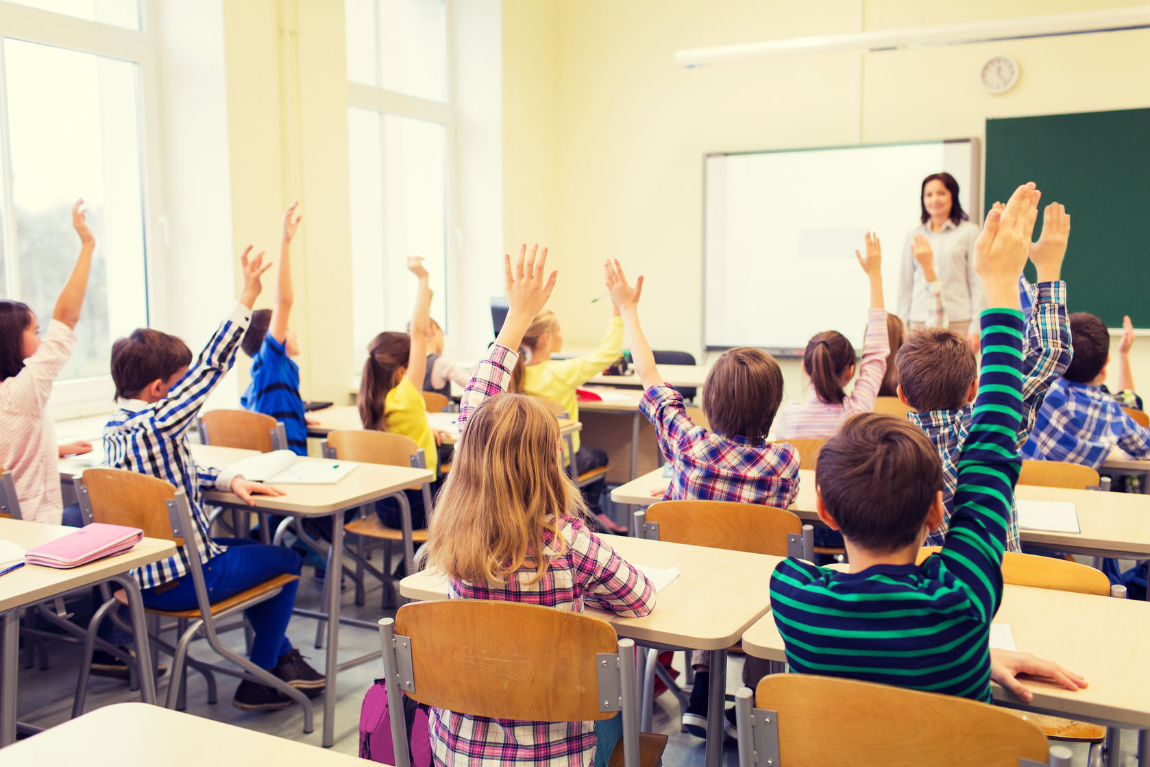 group-of-school-kids-with-teacher-sitting-in-classroom-and-raising-hands.jpg