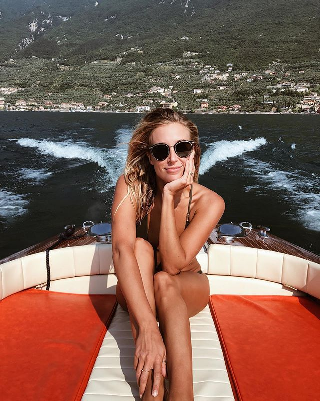 """Just another blonde summering in northern Italy on a 1970's Riva Boat? Claiming La Dolce Vita... not exactly 😂 . . I literally felt myself wanting to mindlessly caption this photo with """"la dolce vita"""" throwing in the overused lemon emoji for good measure. However, I'm currently learning to reprogram my brain at the moment. When I started posting about my travels five years ago """"travel blogging"""" wasn't really a thing. The platform wasn't a place of constant one-uping where comparing makes one depressed, overwhelmed and even anxious. I have been so unbelievably fortunate to see the world in the ways that I have, but I refuse to do so in a way that isn't 100% representative of what I experience and how I feel. . . Last year I was so overwhelmed by the constant pressure for perfection, and capturing the moment in the MOST epic way, that I lost my direction and felt that I was no longer exploring, living and experiencing just for me. It was for my account and the people watching me. . . Now that's some bullshit. So I am taking steps to reprogram how I engage, post, and even who I follow... because I'm a sensitive being who often feels depleted and irritated by social media. . . While this is still an honest photo of me happily enjoying my time on beautiful Lake Garda, I just wanted to be more open about who I truly am in a more well rounded way. Thanks for the love and support thus far! Stay tuned... ✨🙏🏼💙"""