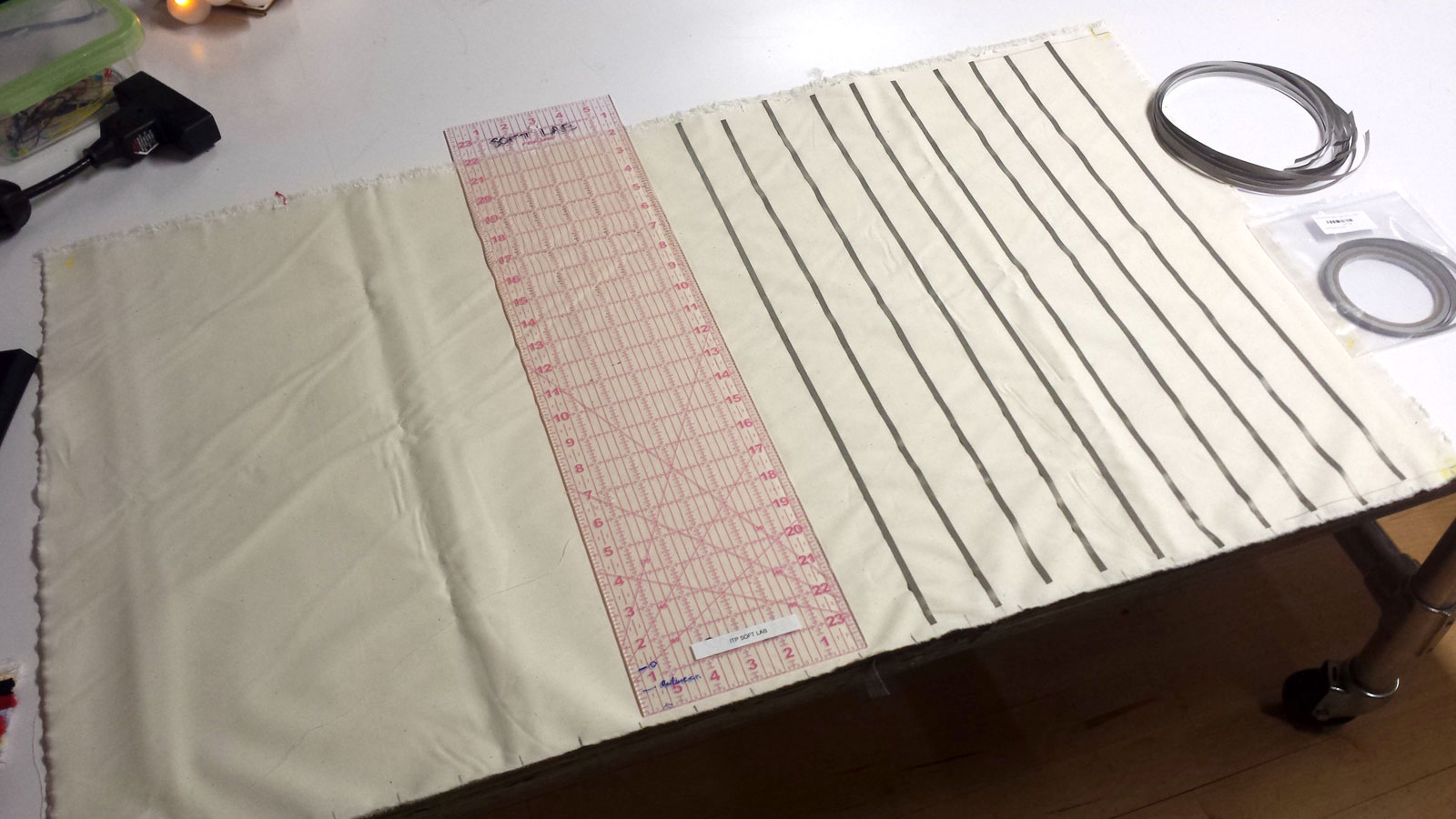 Placing thin strips of conductive tape onto canvas