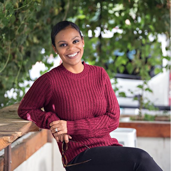 Three quarter headshot image of female, African American business owner in red sweater.