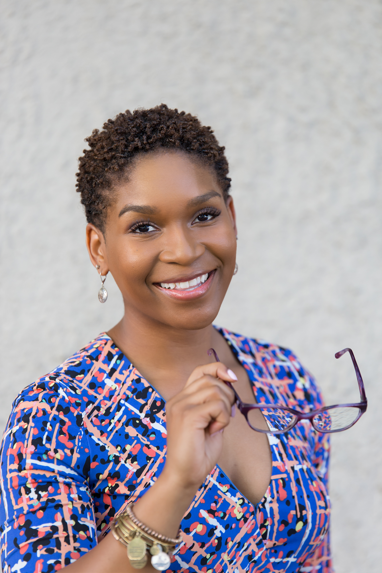 Headshot of female, African American, social media marketing consultant holding glasses and smiling.