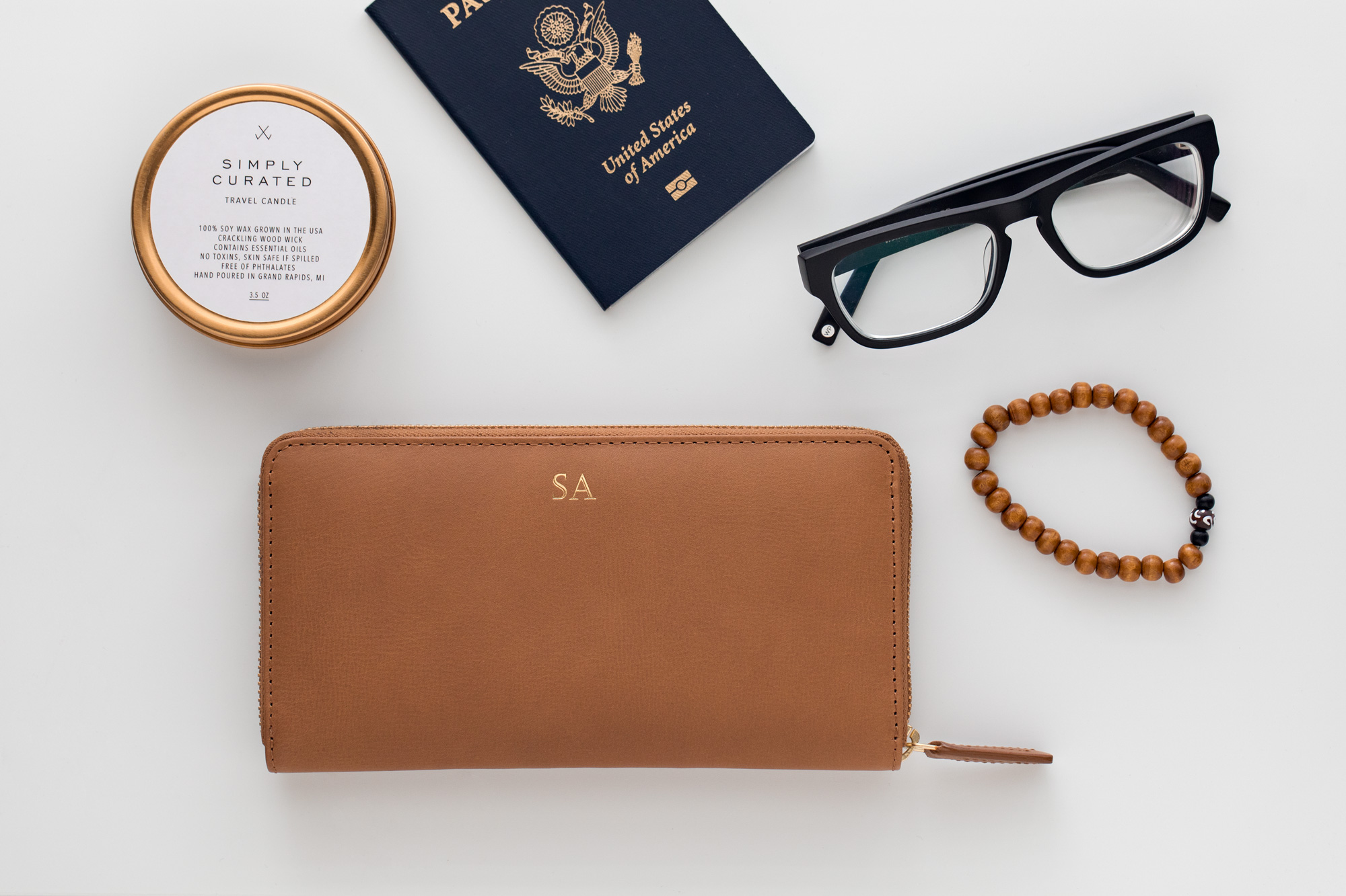 Flat-lay photo of monogramed, leather wallet, simply curated travel candle, warby parker glasses, and beaded bracelet.