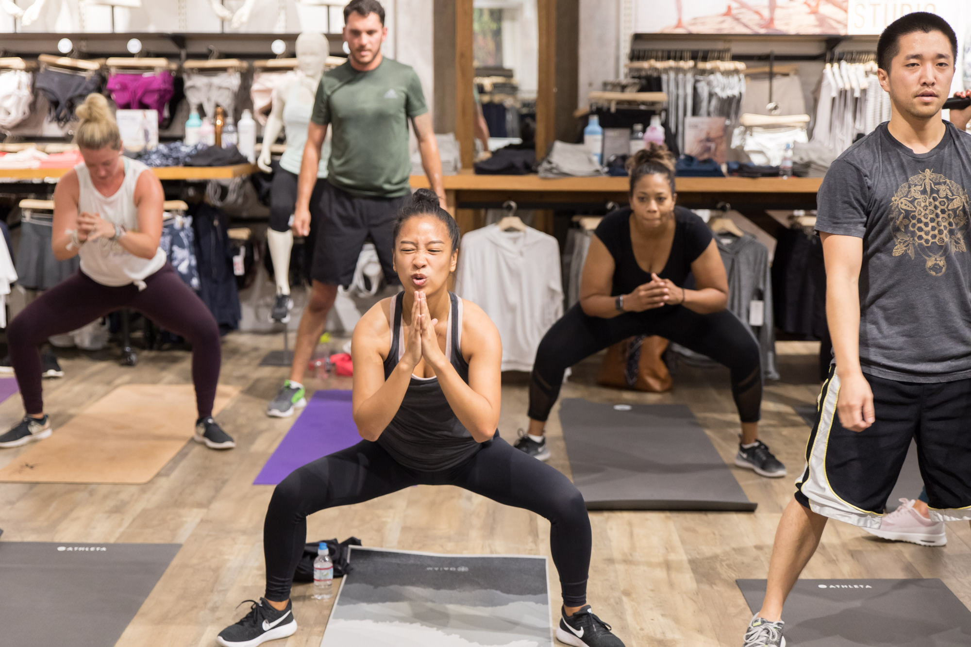 strained-face-attendee-doing-squats-during-group-fitness-workout-pop-up-athleta-san-jose-valley-fair-mall.jpg