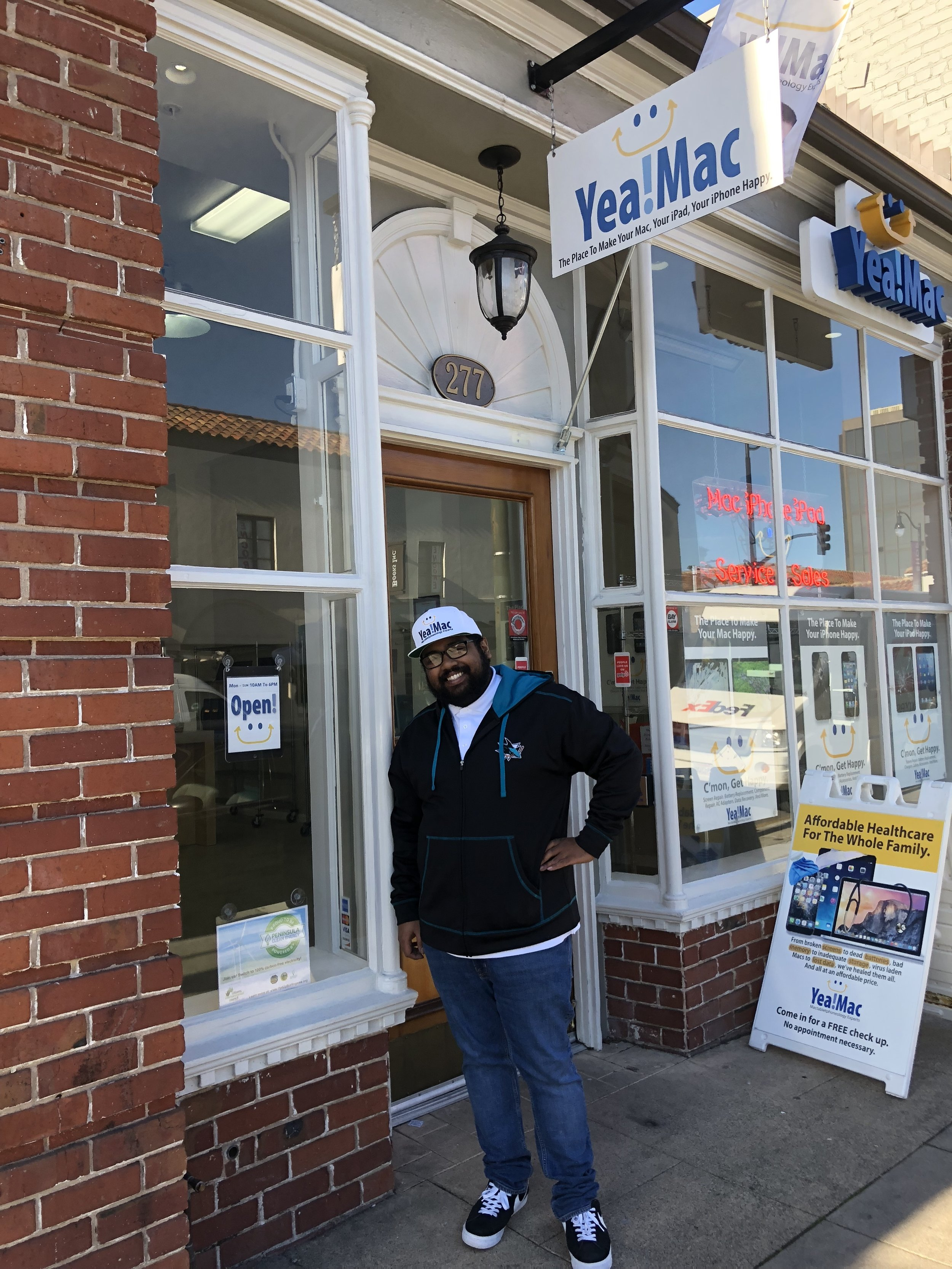 Yea!Mac employee next to #OptUpBurlingame sign.