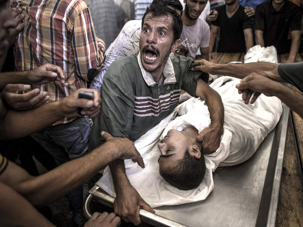 A father cries over the body of his son who died when the UN school for refugees in Beit Hanoun was attacked [ MORE ]