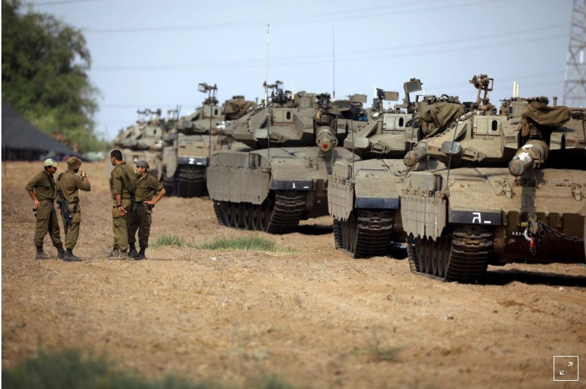 Israeli soldiers speak next to tanks as military armoured vehicles gather in an open area near Israel's border with the Gaza Strip October 18, 2018