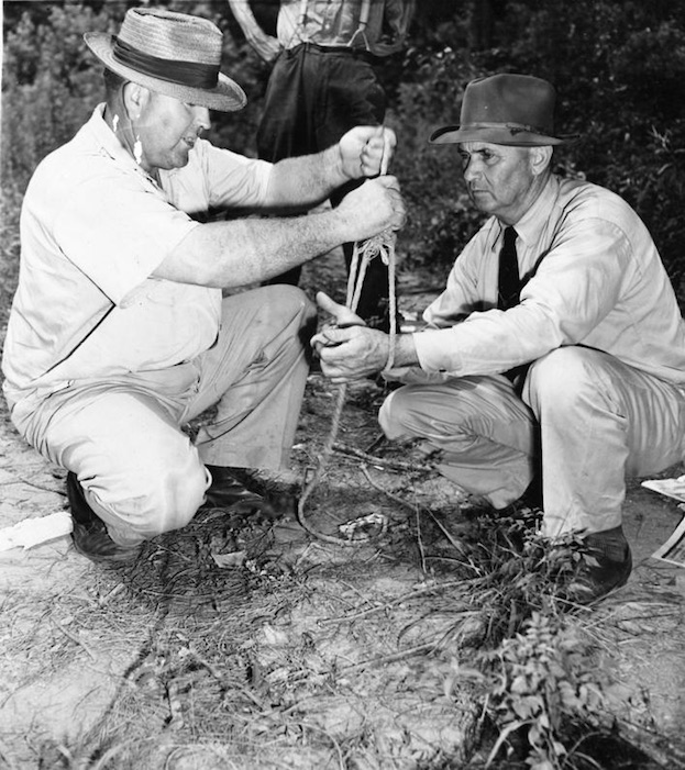 July 26, 1946 -- Loy Harrison (left), an Oconee County farmer, shows Sheriff J.M. Bond of Oconee County how the mob bound the hands of the two black male victims, George Dorsey and Roger Malcom, together before shooting them and their wives to death near Monroe, Ga., July 25, 1946. Harrison said the mob took the four victims from his car as he was driving to his farm. [   MORE   ]