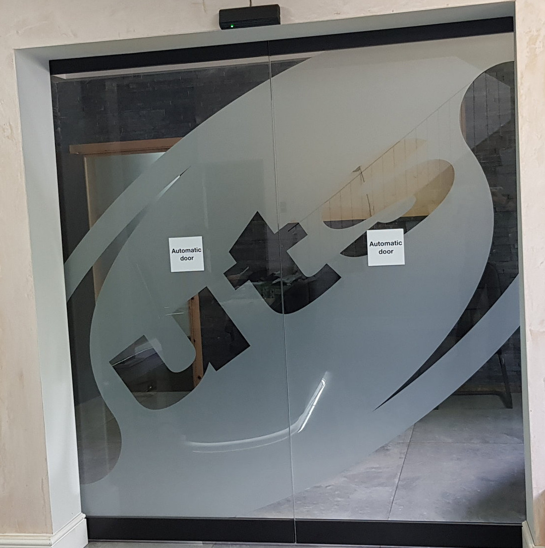UTS   Frosted window graphic of a company logo fitted across a glass double door.