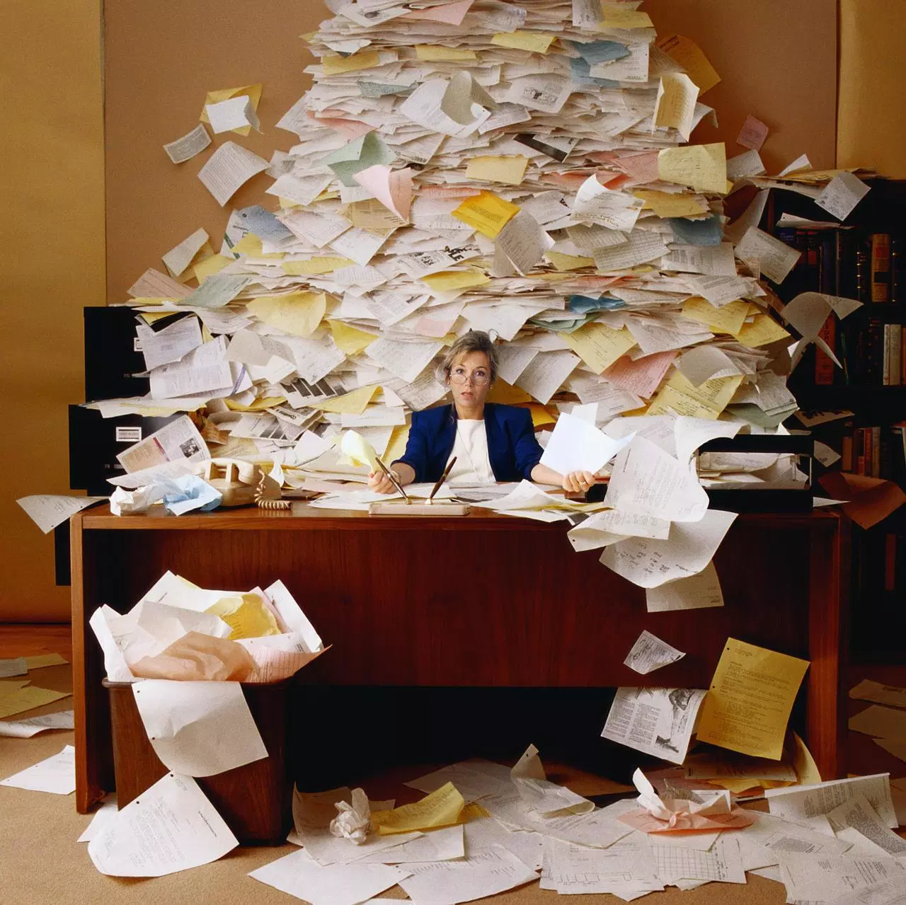 Woman sat at desk surrounded by flood of paper documents