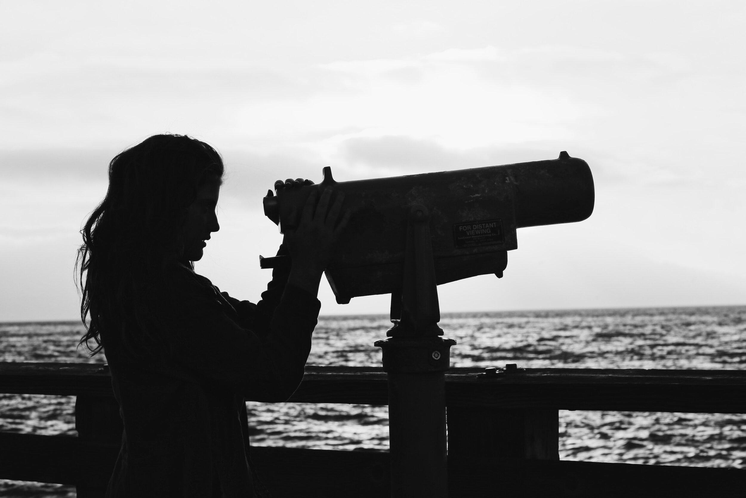穿过望远镜的女性