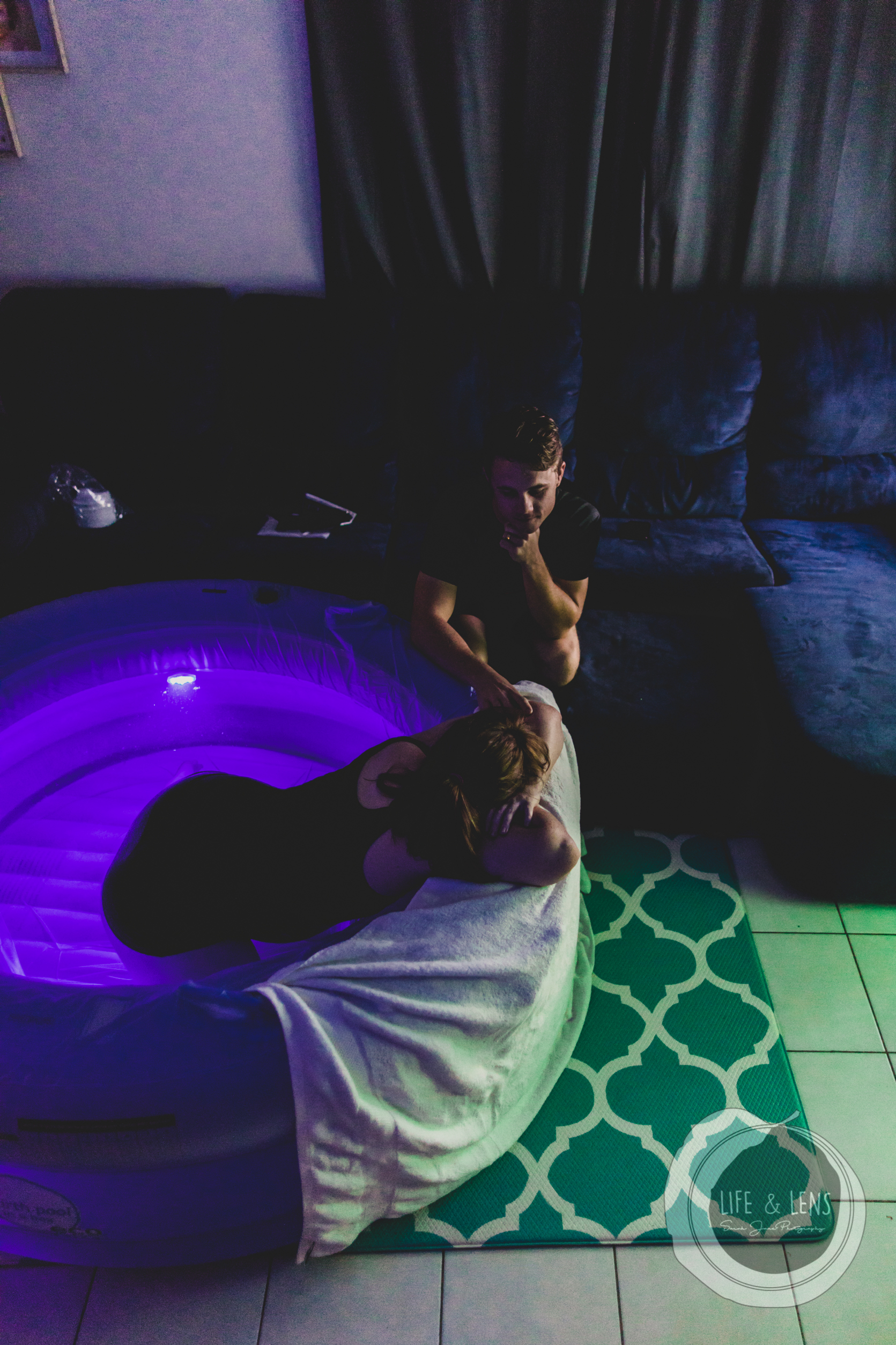 sydney birth photographer - mother in home waterbirth being supported by dad