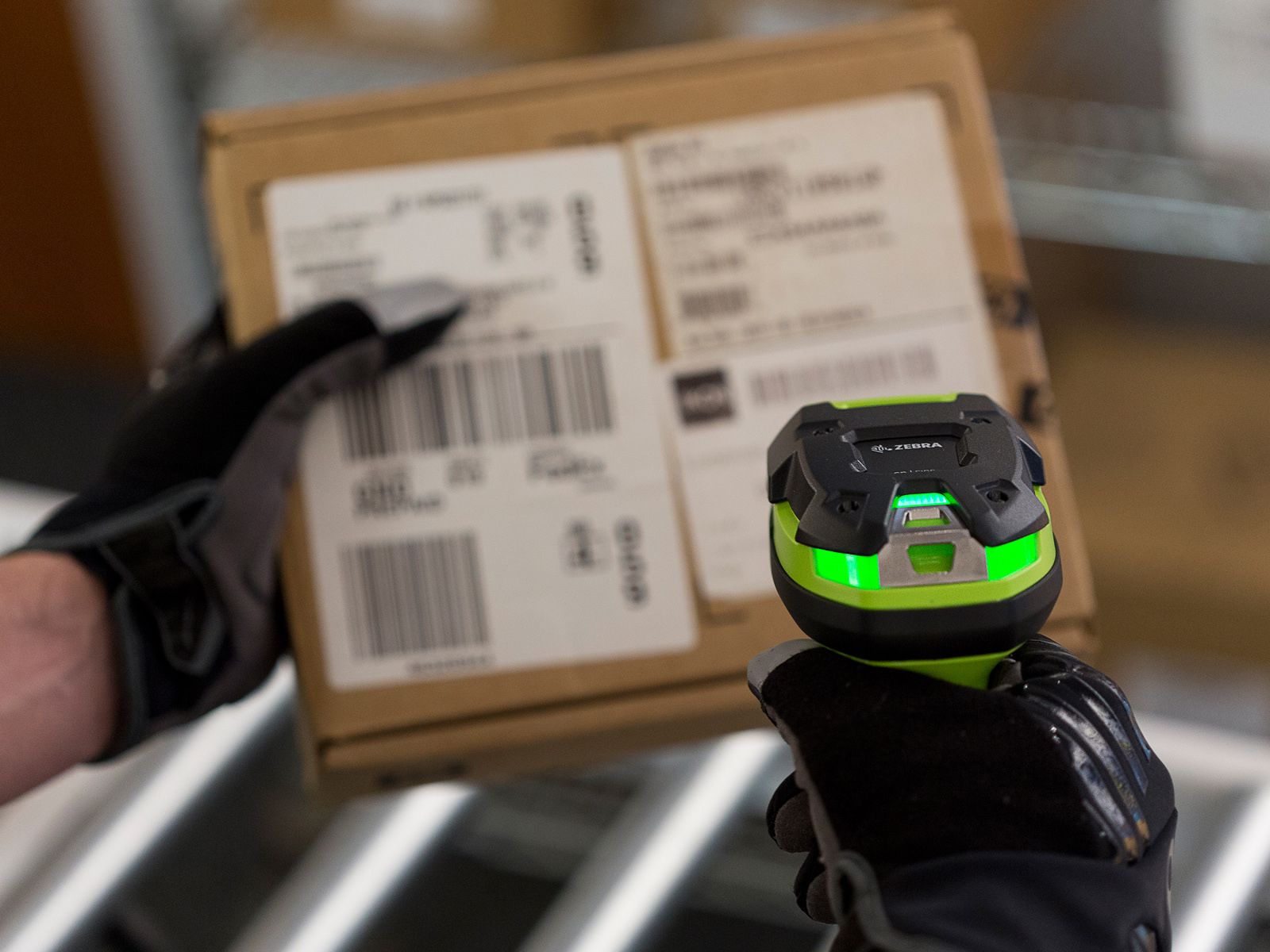A 3600 scanner being used by a glove-wearing person to scan a barcode on a box
