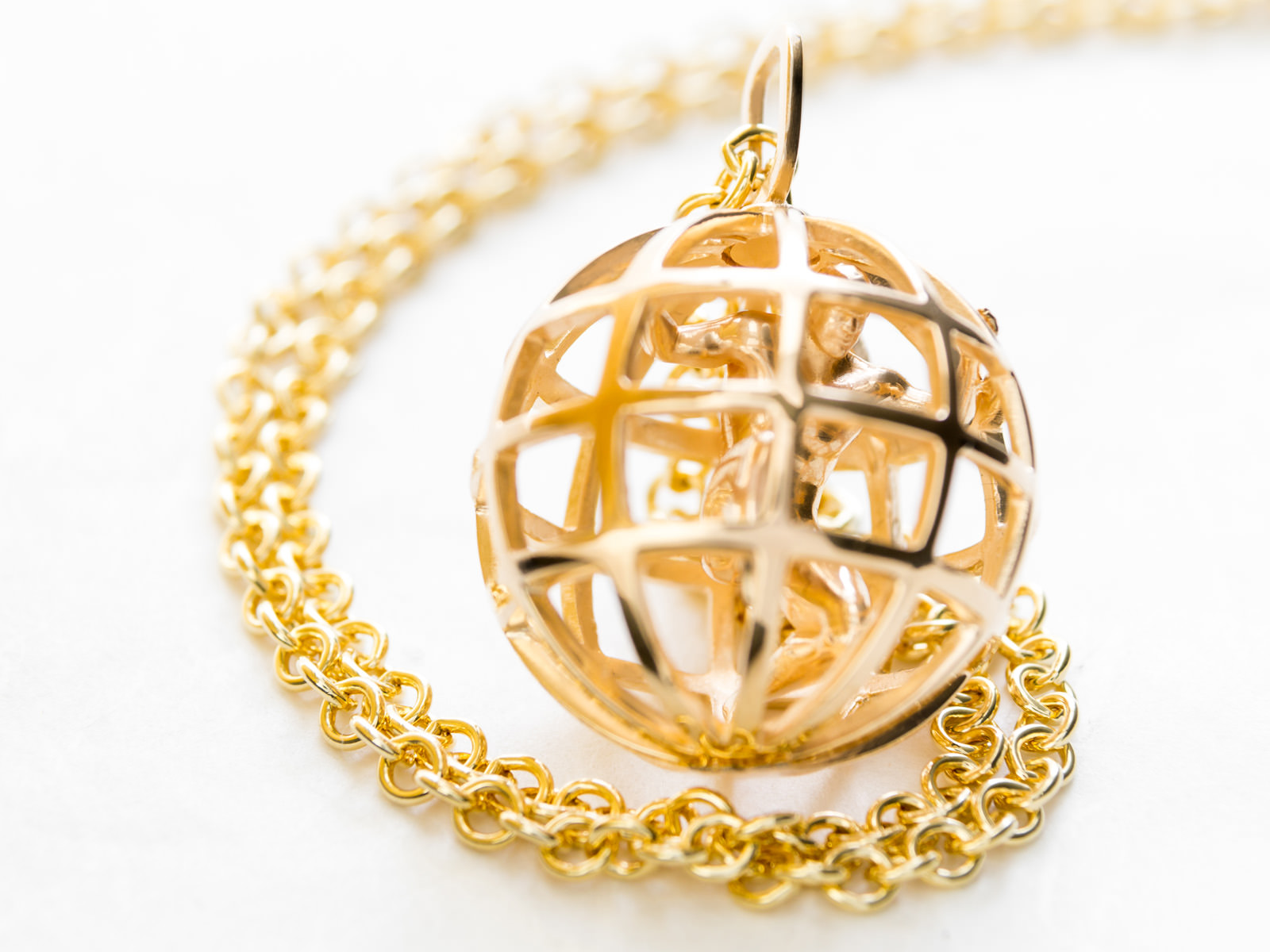 The gold Atlas pendant where a man is enclosed inside a cage-like ball