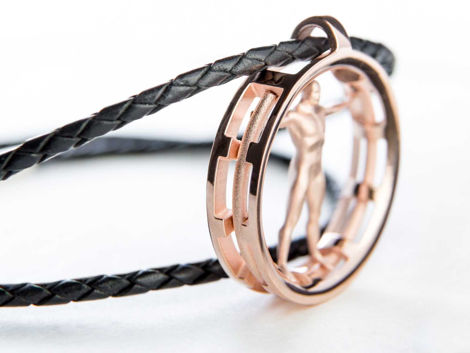 A rose gold Vitruvian man pendant with leather cord attached