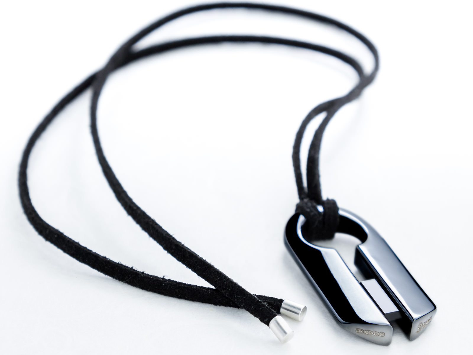 The Pincer pendant lying on a table with the leather cord laid out in an arc around it