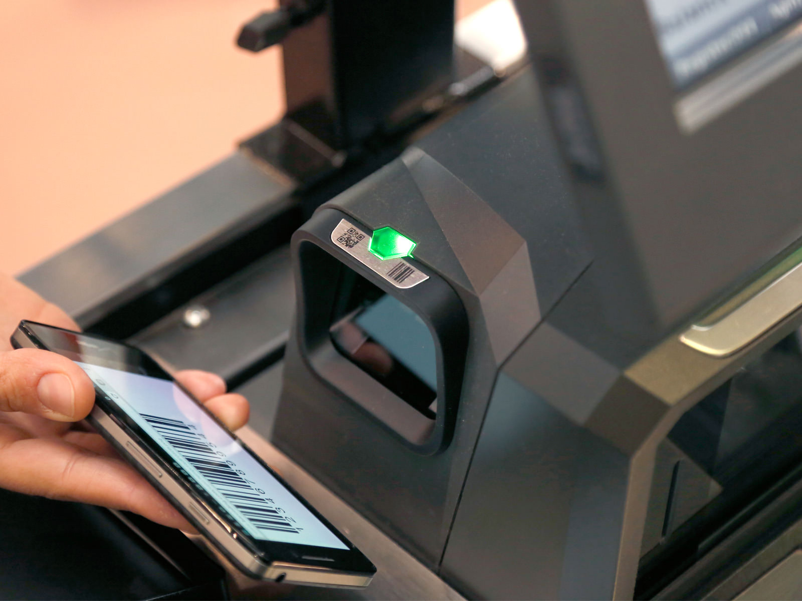 Presentation of a smart phone with barcode on screen to the side mounted barcode scanner