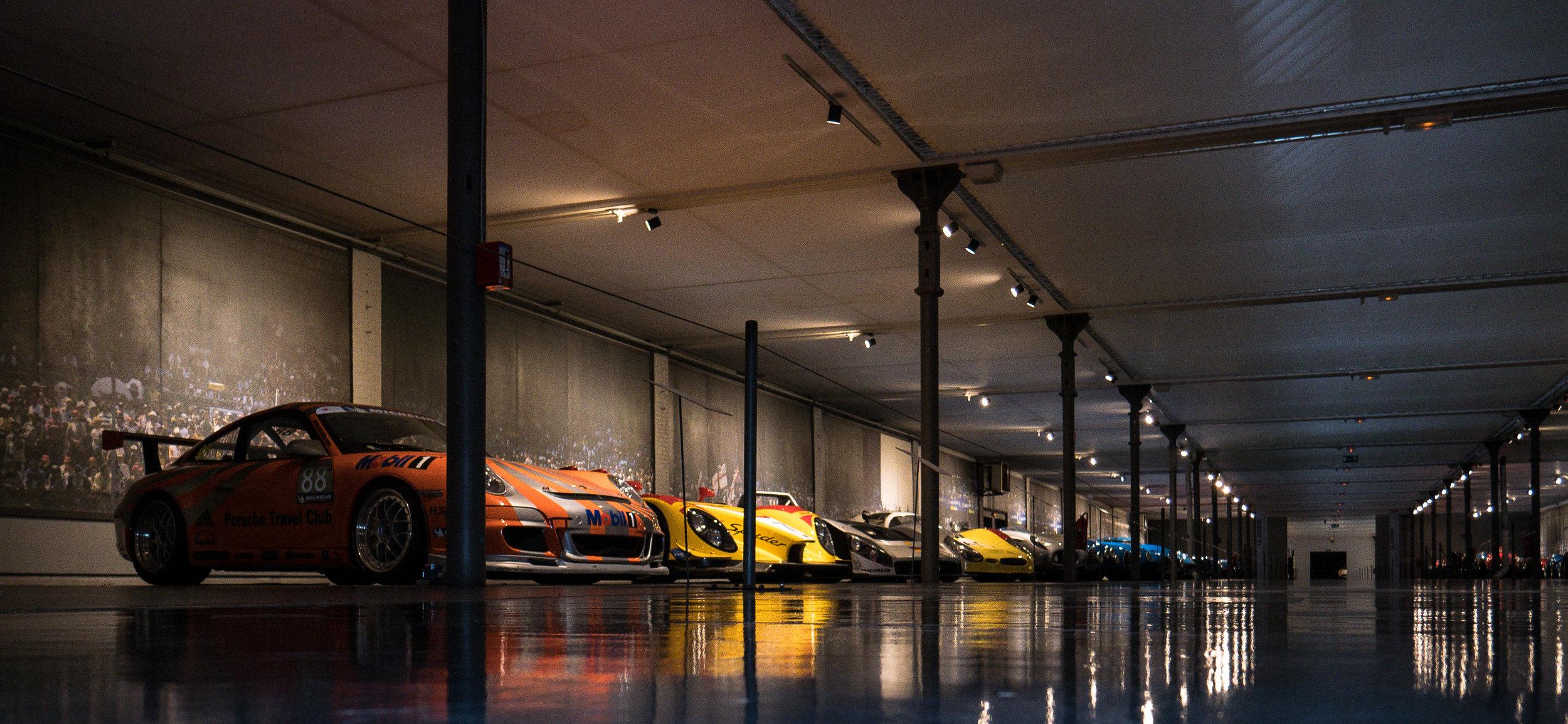 Multiple modern race cars displayed in a long, low ceiling room (Credit: Nicolai Rauser)